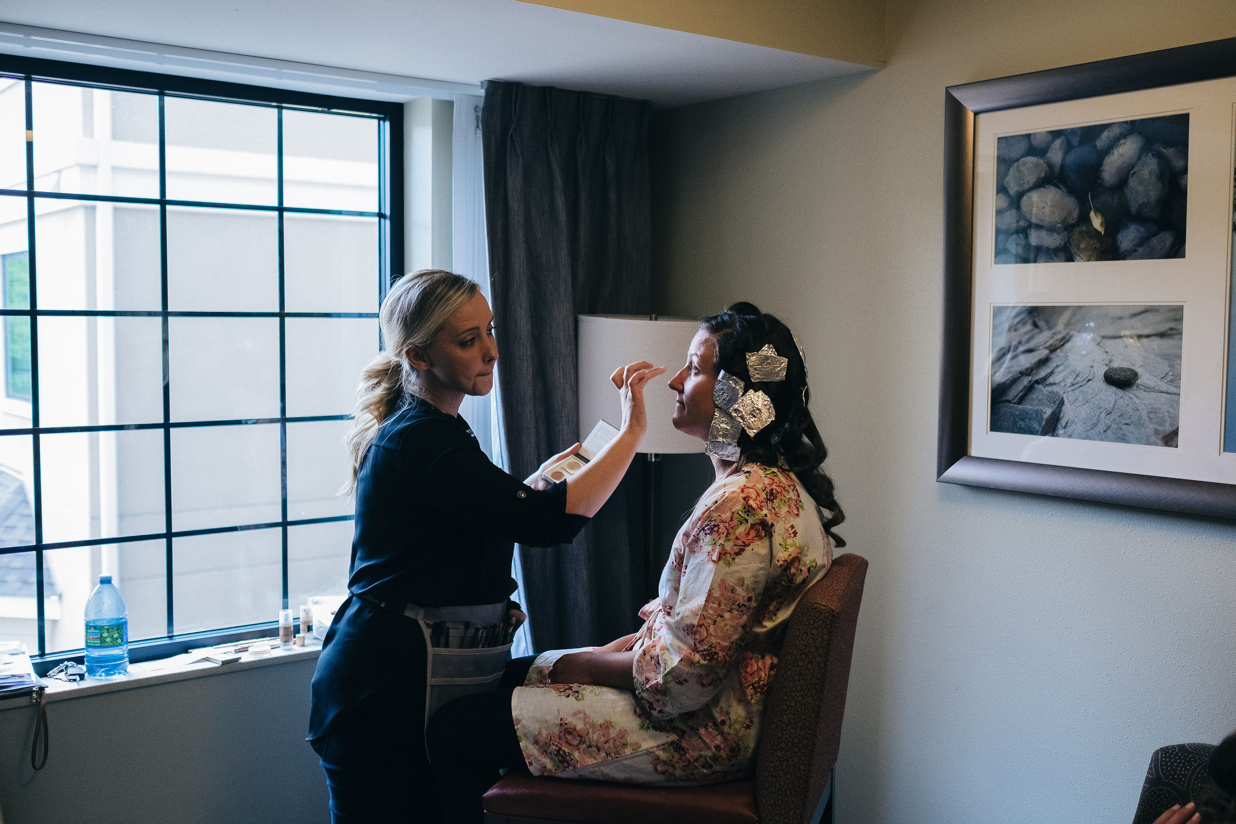 Bride gets makeup done before ceremony at hotel in Canton, Ohio.