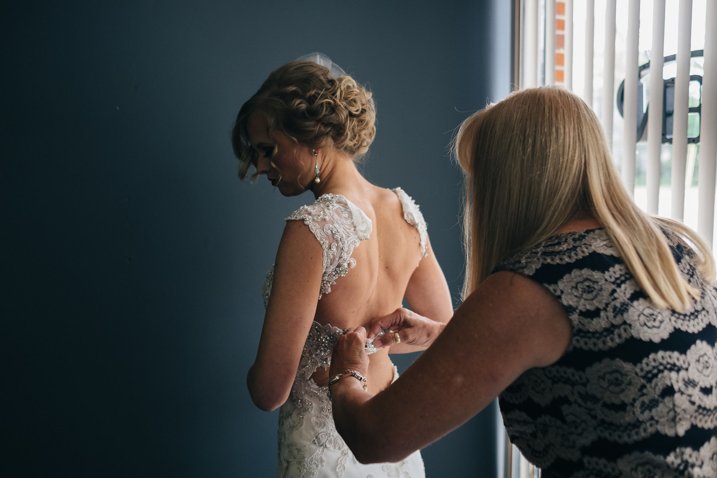 Bride getting into Maggie Sottero dress for wedding at Mon Ami Winery.