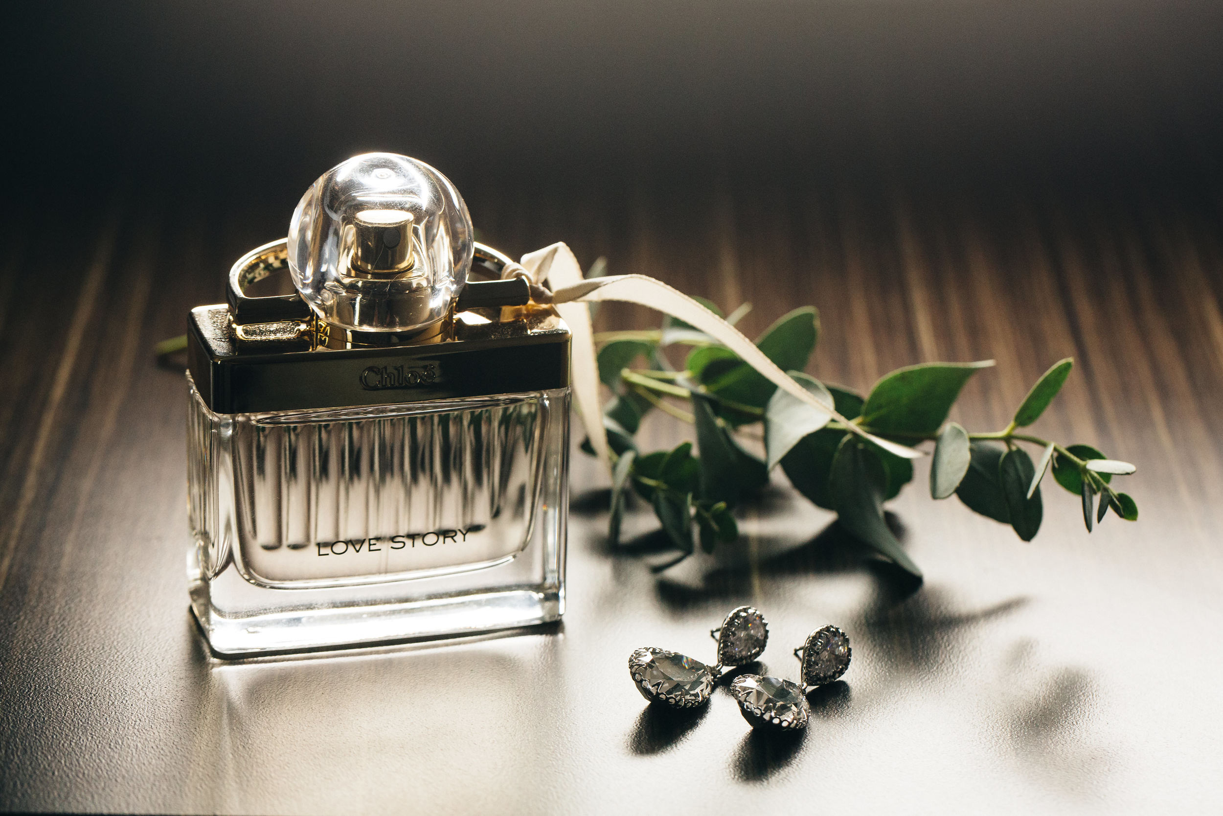 Brides perfume bottle and ear rings on wedding day.