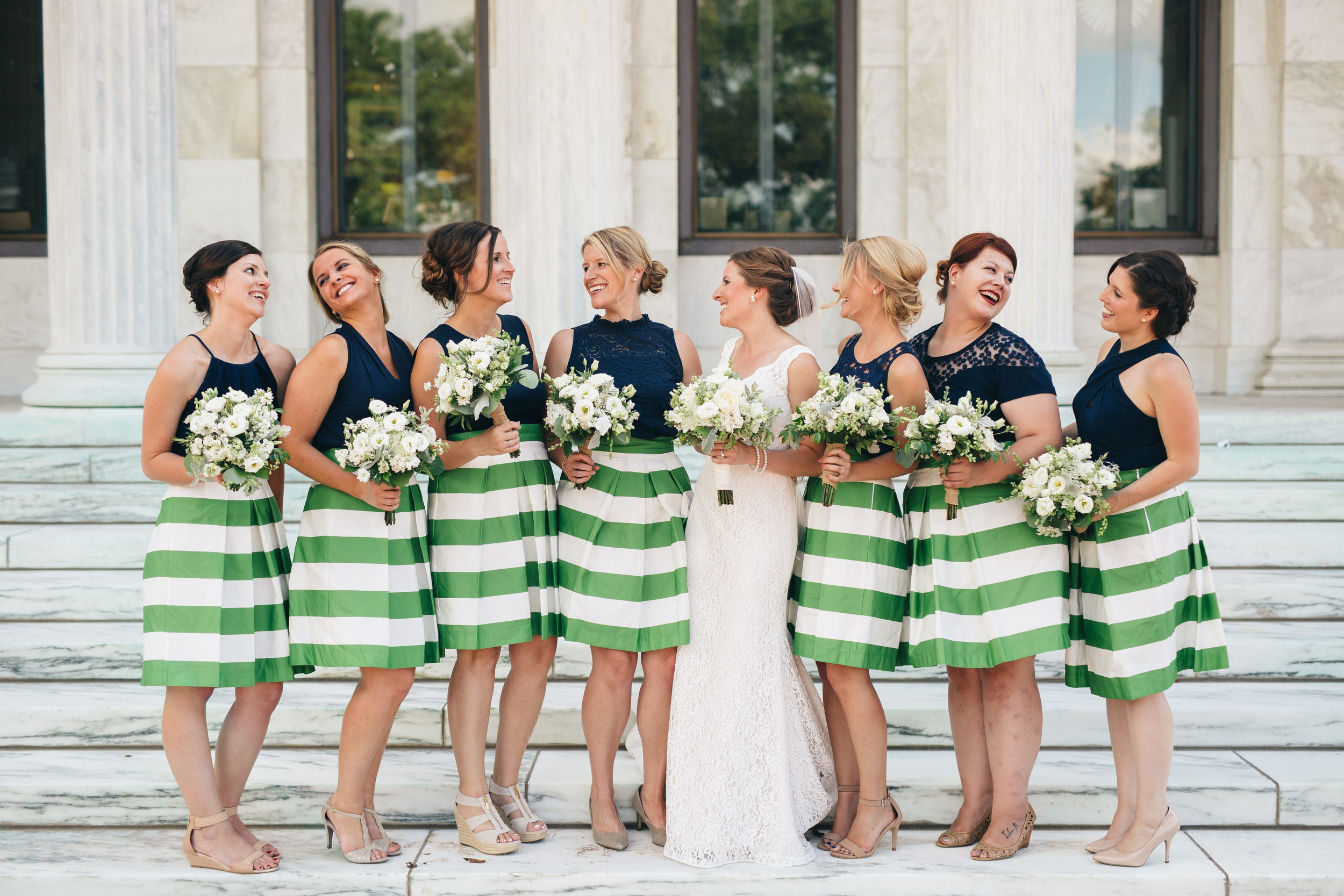 Gorgeous bridesmaid in kelly green striped skirts and navy blue tops.