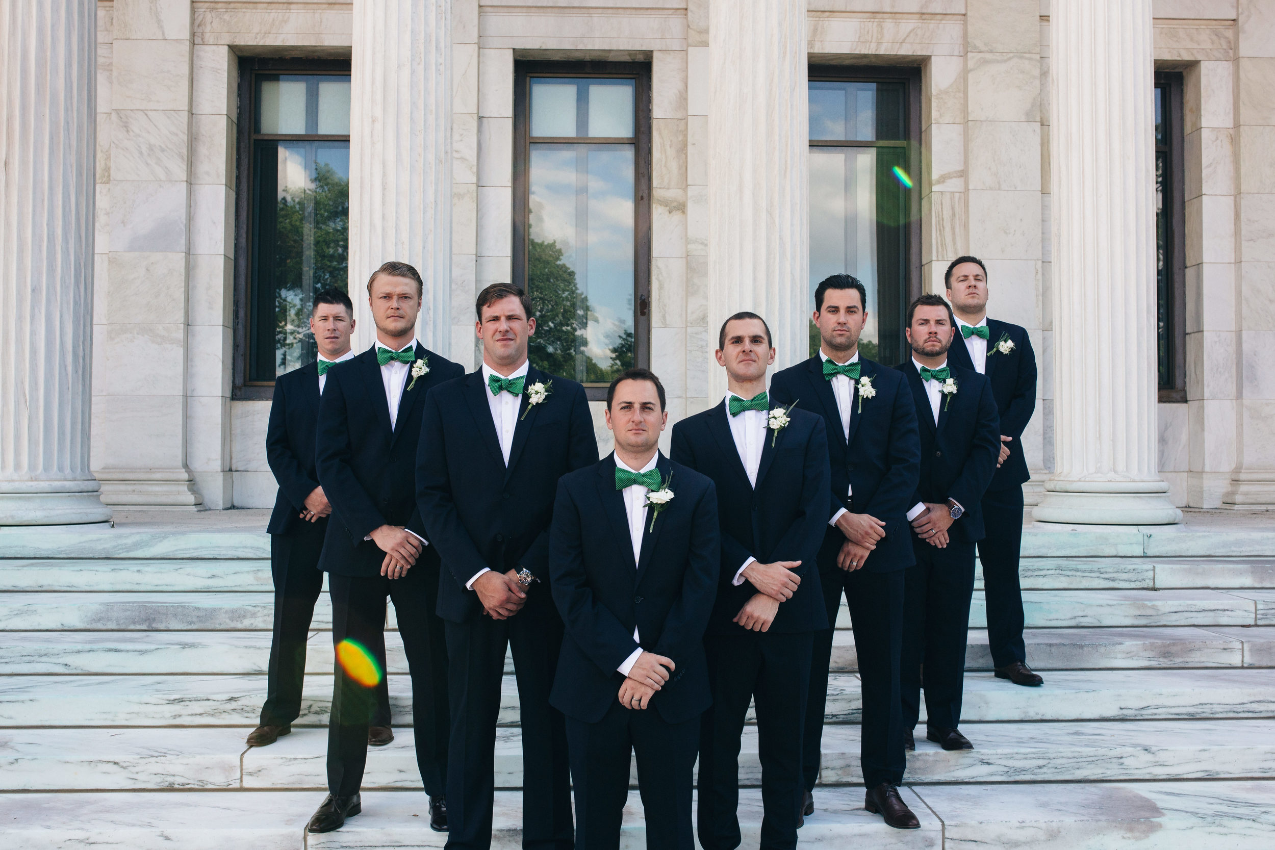 Groomsmen in black suits and kelly green bow ties.
