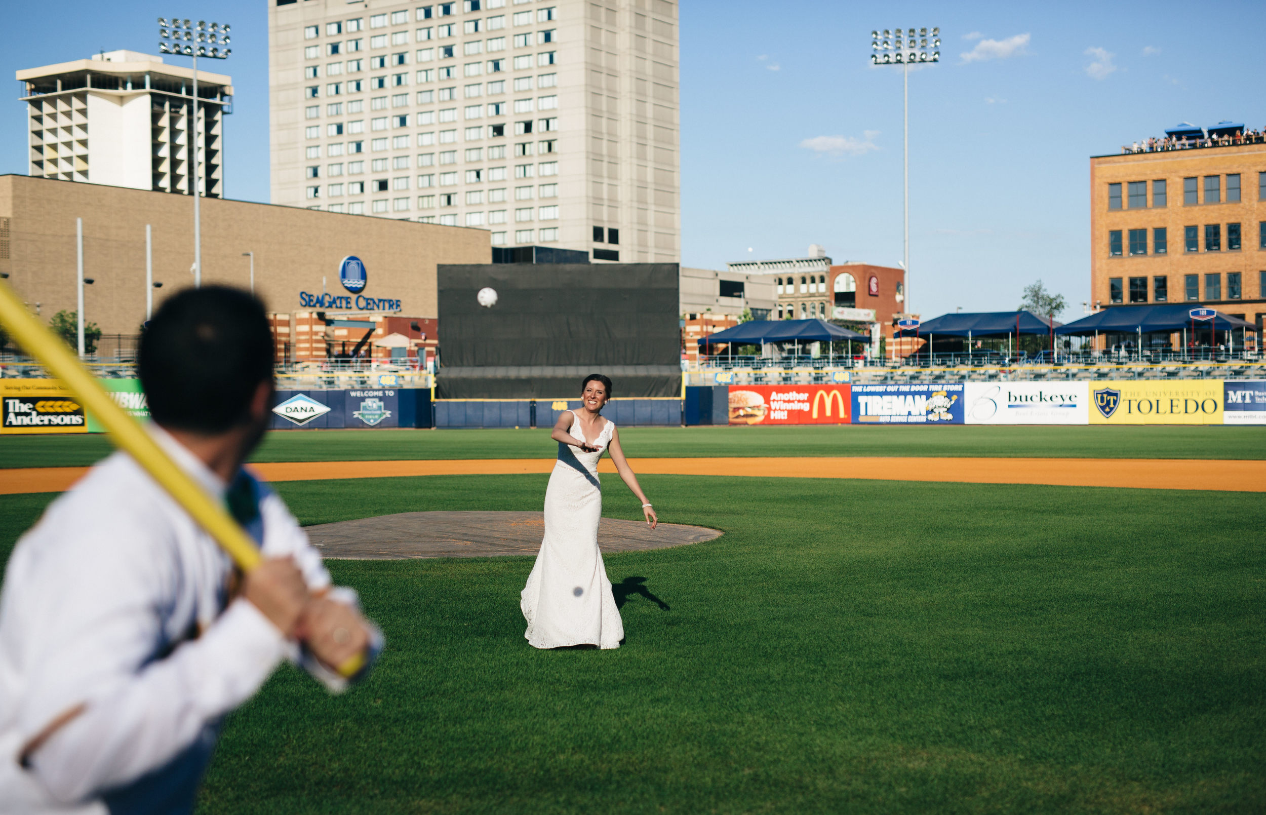 Bride pitches to groom at Fifth Third Field during Hensville Wedding.