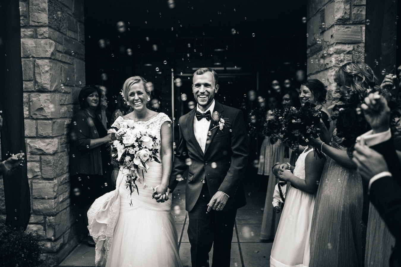 Black and white portrait of bride and groom exiting ceremony.
