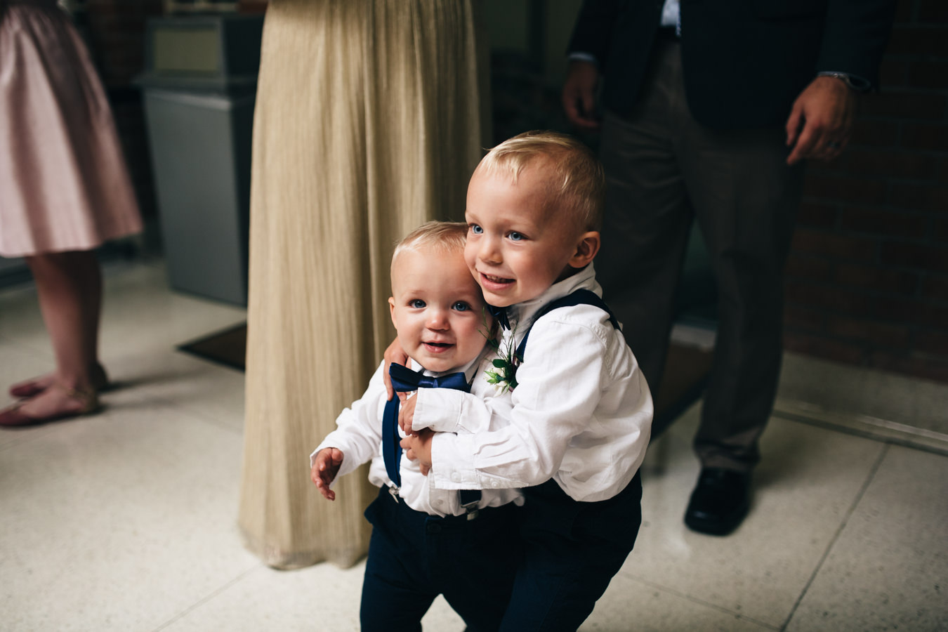 Two cute ring bearers in bow ties and suspenders