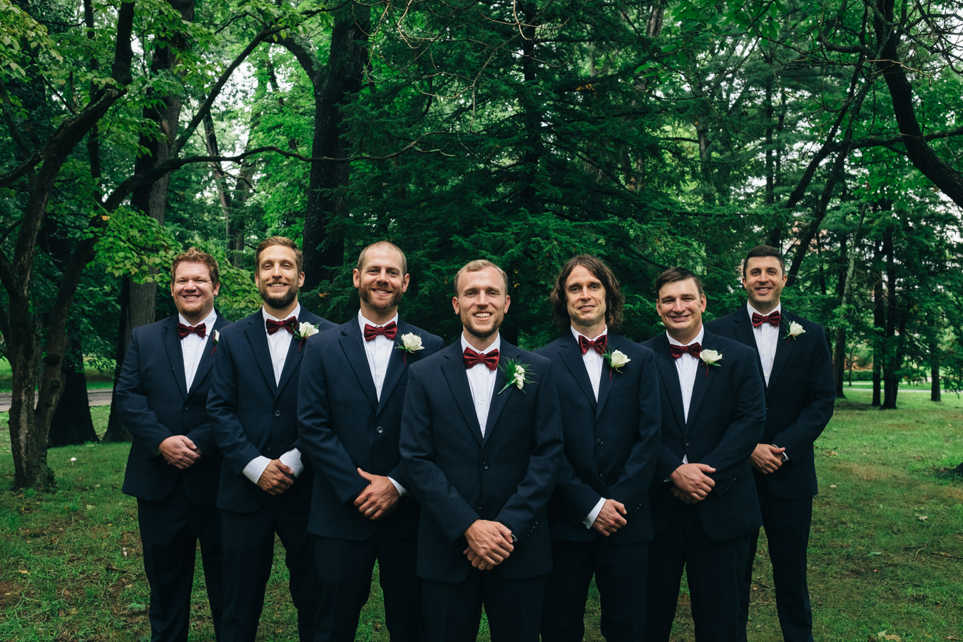 Groomsmen in black suits and merlot bow ties.