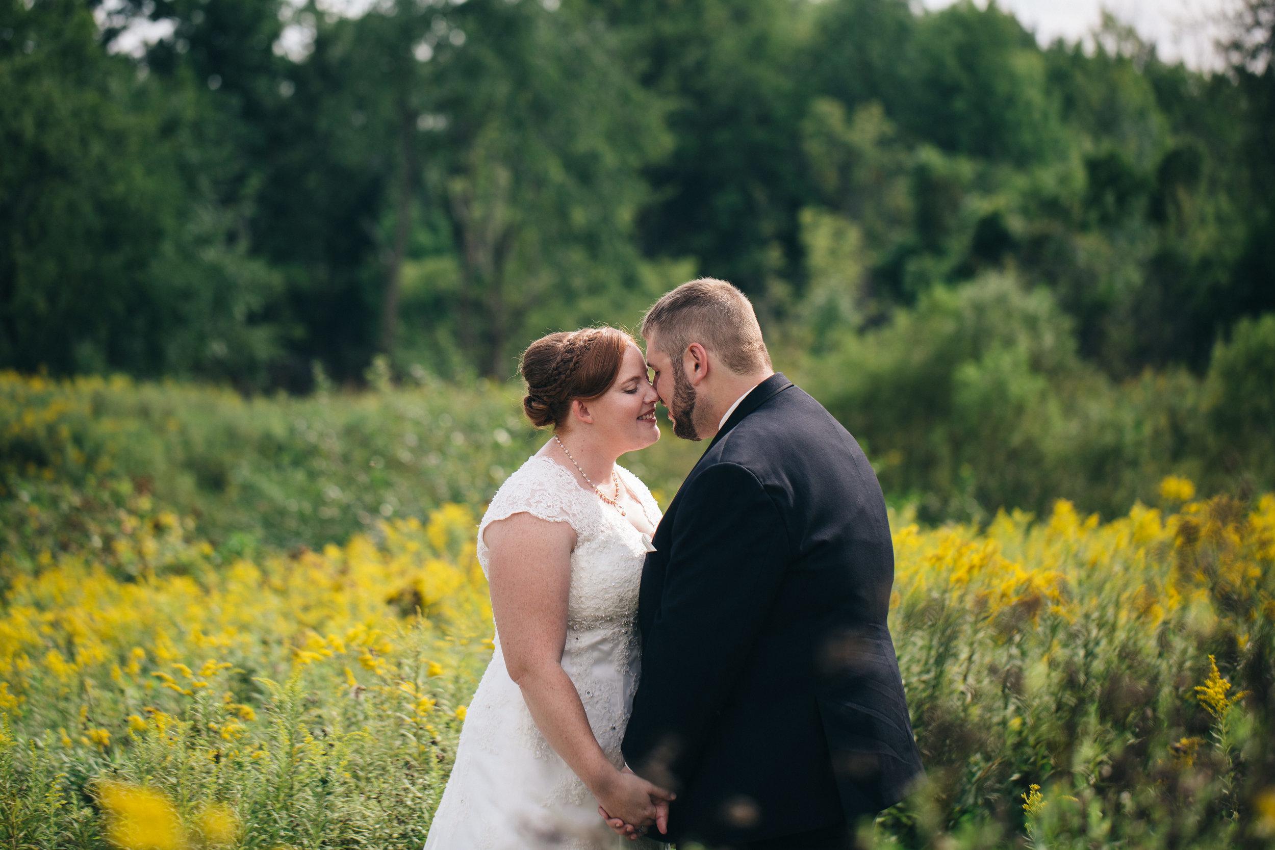 Bride and groom in wildflowers at Walden Inn & Spa.