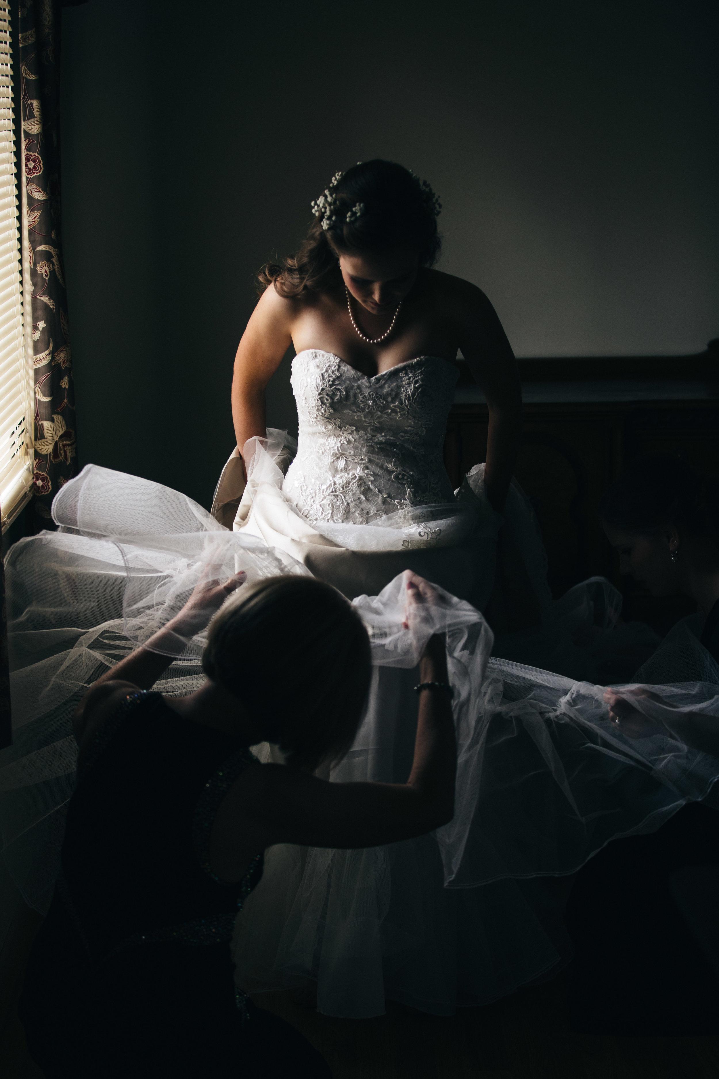 Bride getting into wedding dress.