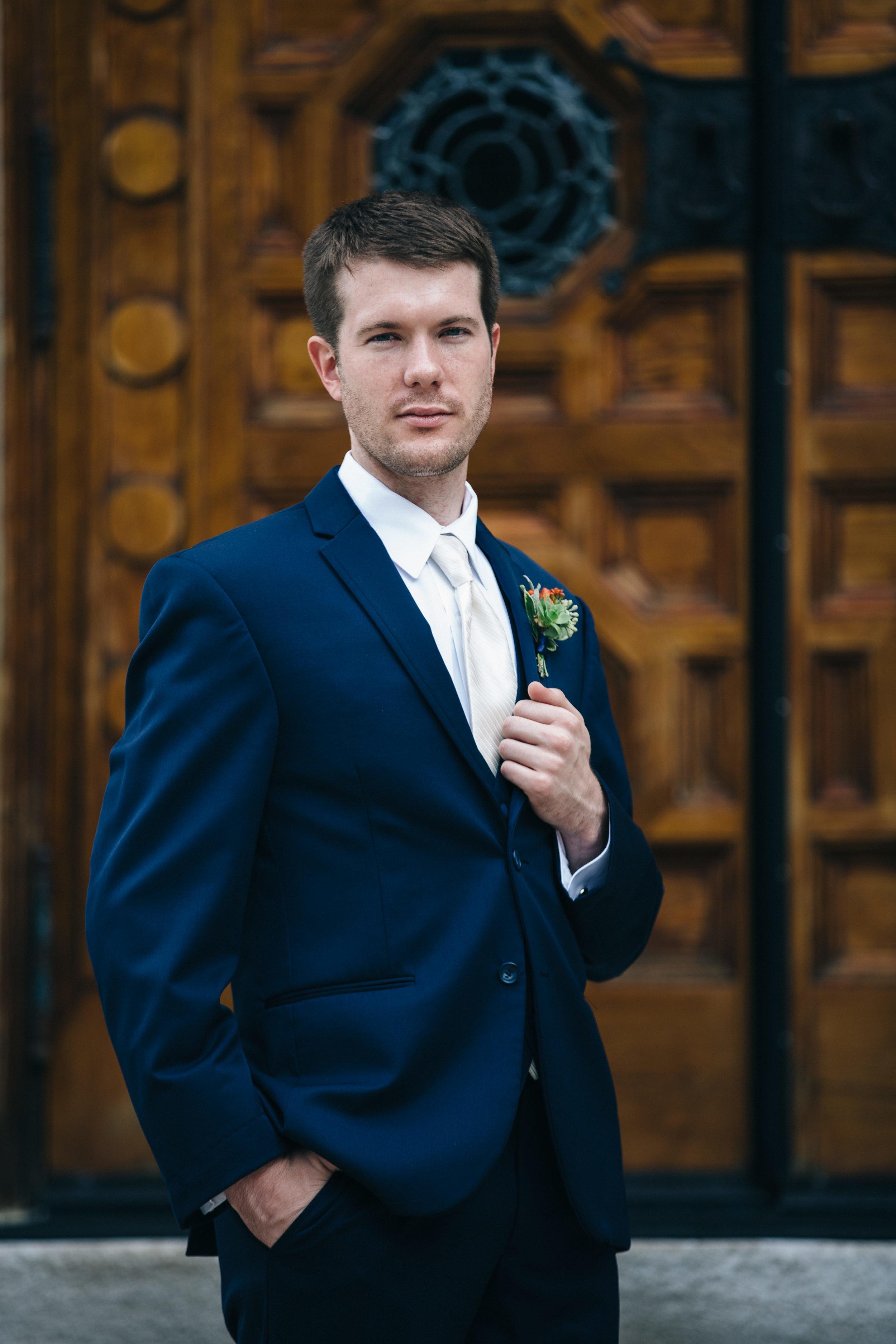 Wedding photography of groom in navy blue suit.