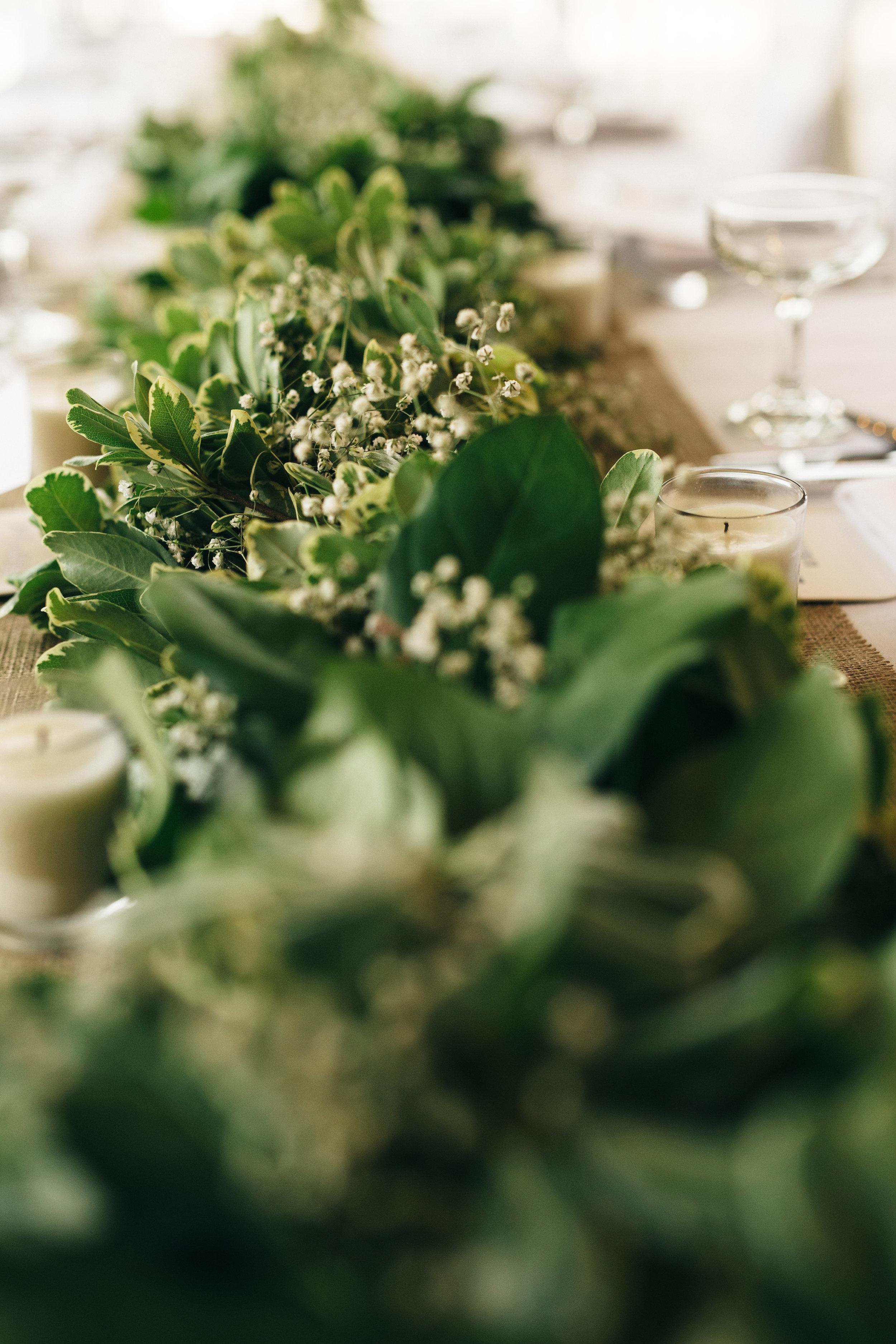 Floral arrangement full of wedding greenery.