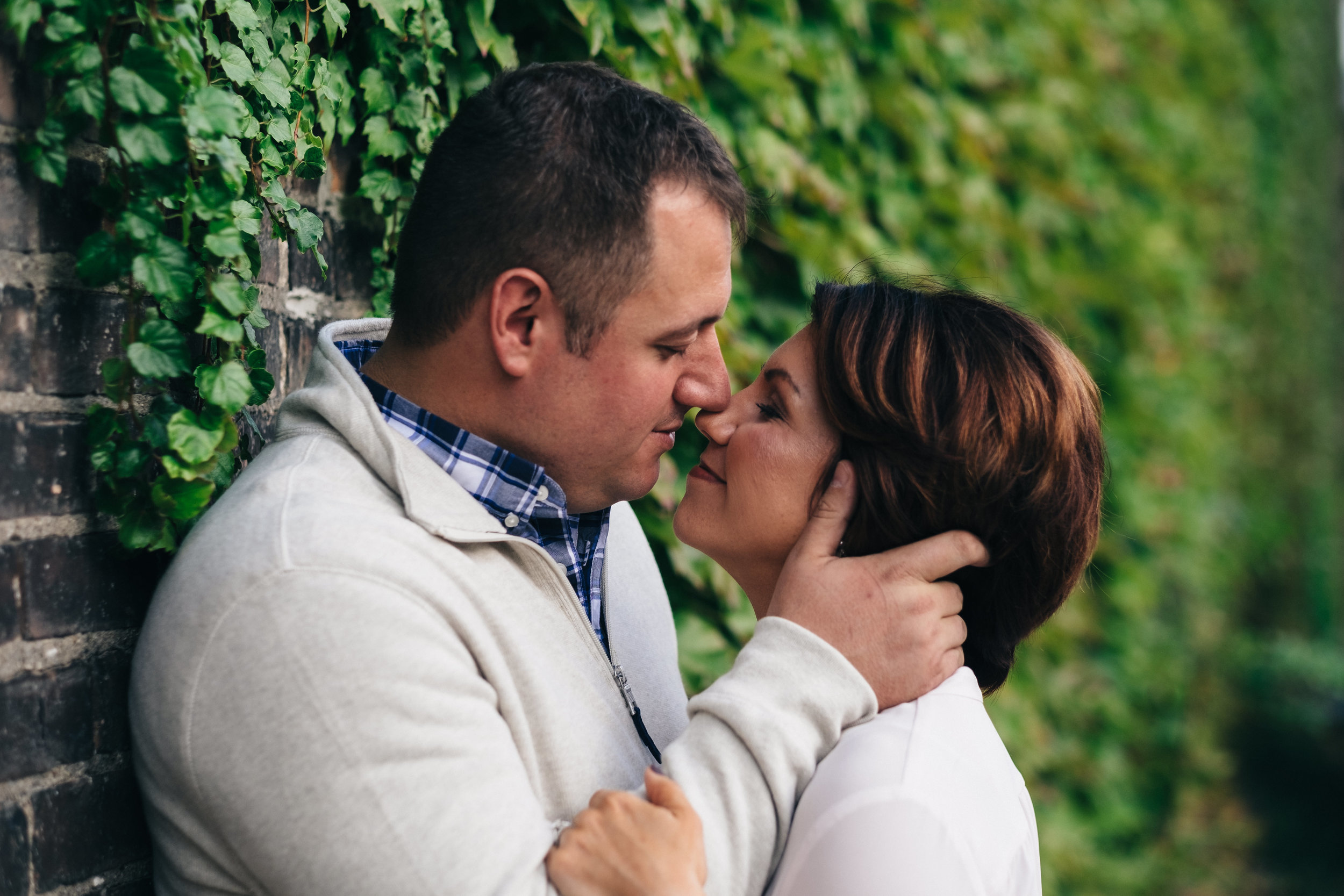 Engagement session in downtown Toledo in front of greenery wall.