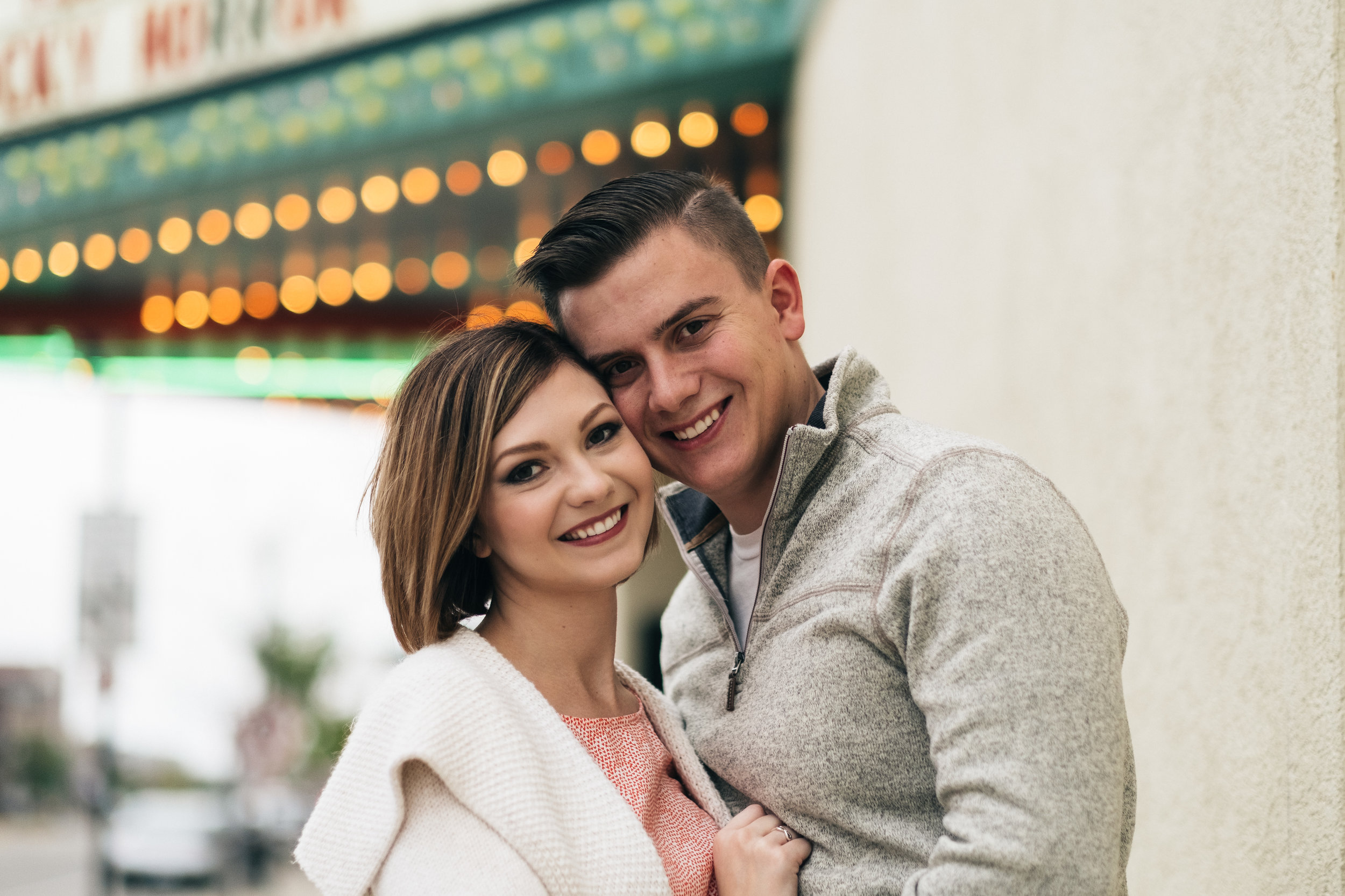 Smiling engagement picture in front of urban movie theater in Royal Oaks, Michigan.