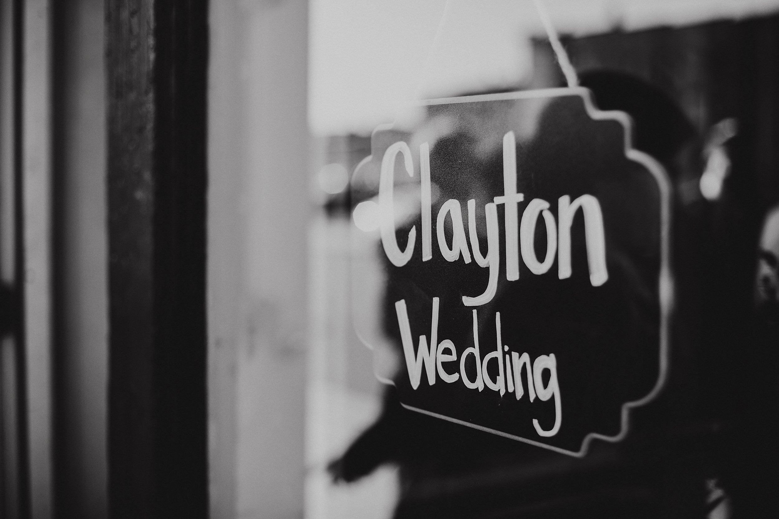 Chalkboard wedding sign hanging in window at venue.