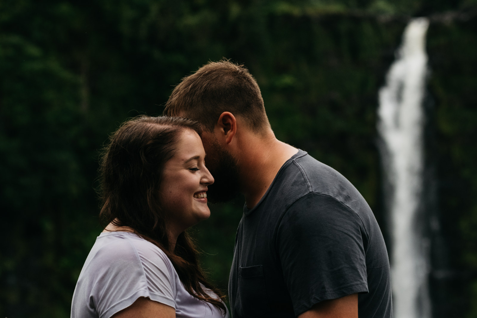 Intimate engagement photos near a waterfall in Kailua-Kona, Hawaii.