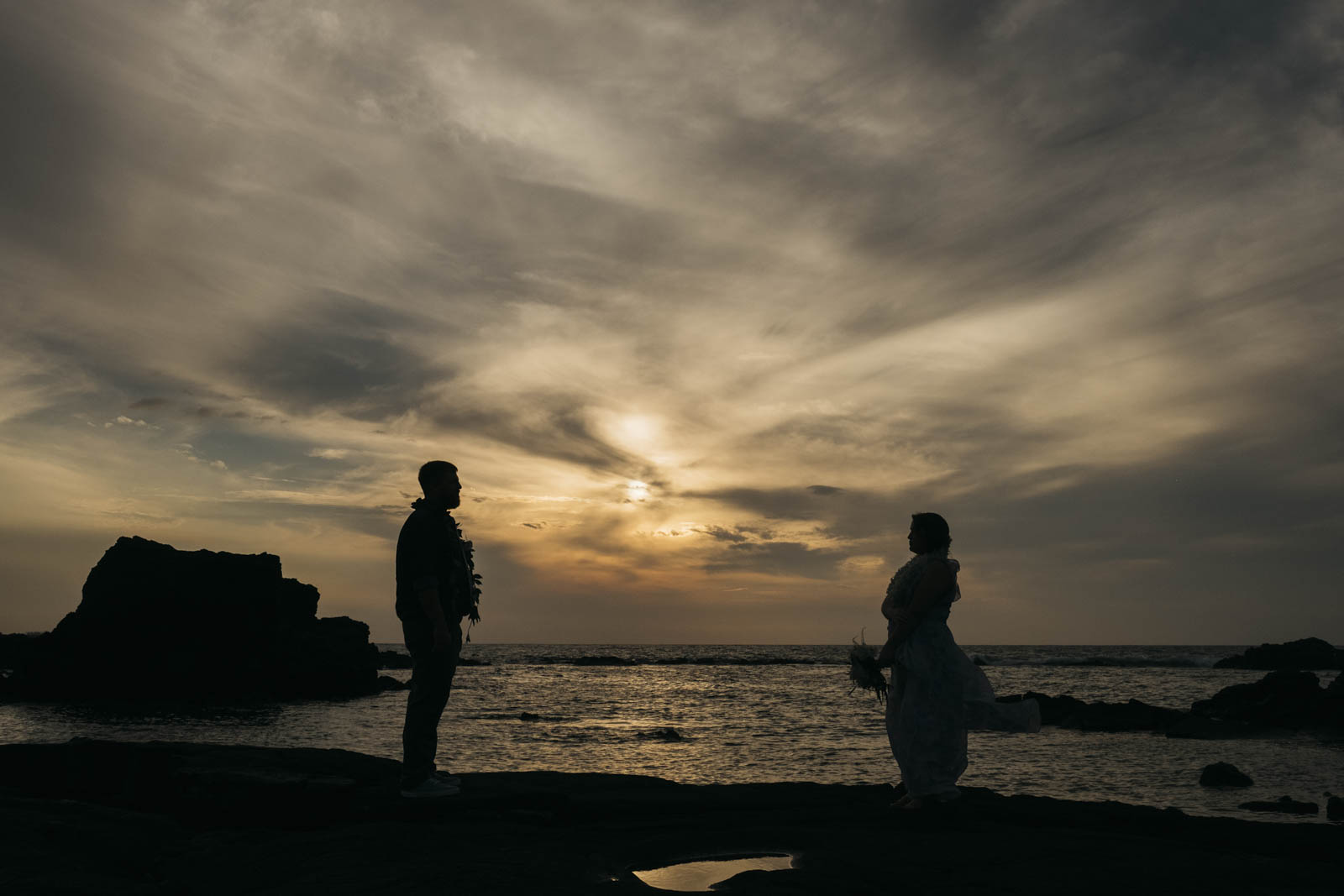 Bride and groom sunset silhouette portrait.
