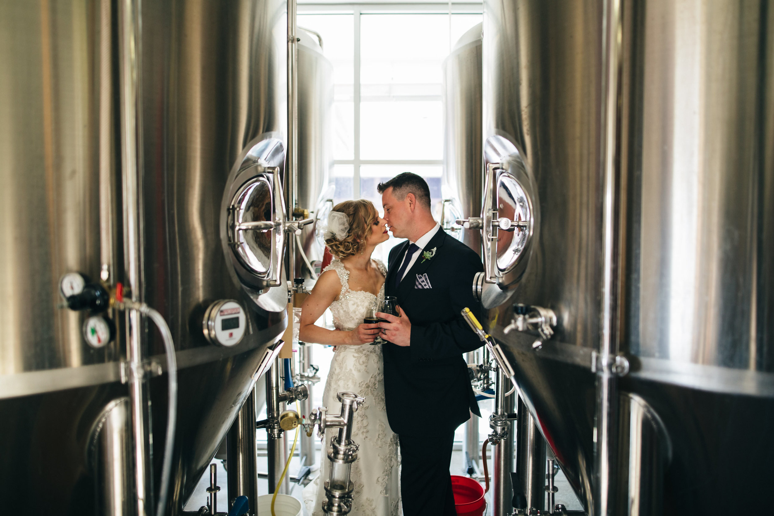 Bride and groom kissing at local brewery
