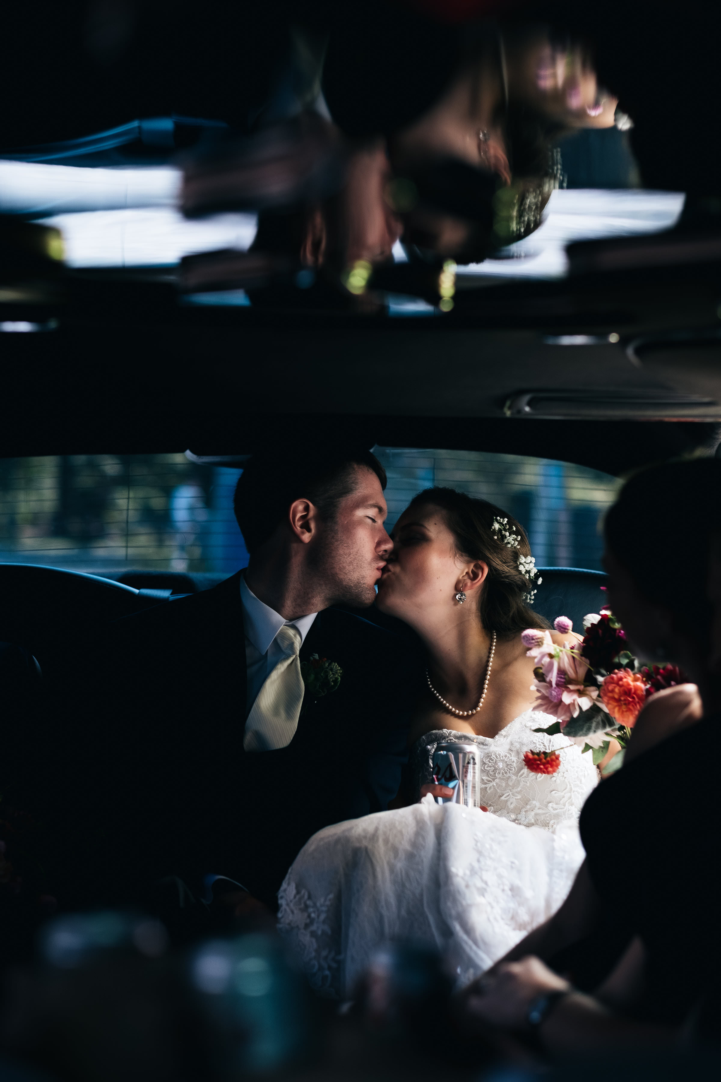 Bride and groom kissing in the back the of a limo.