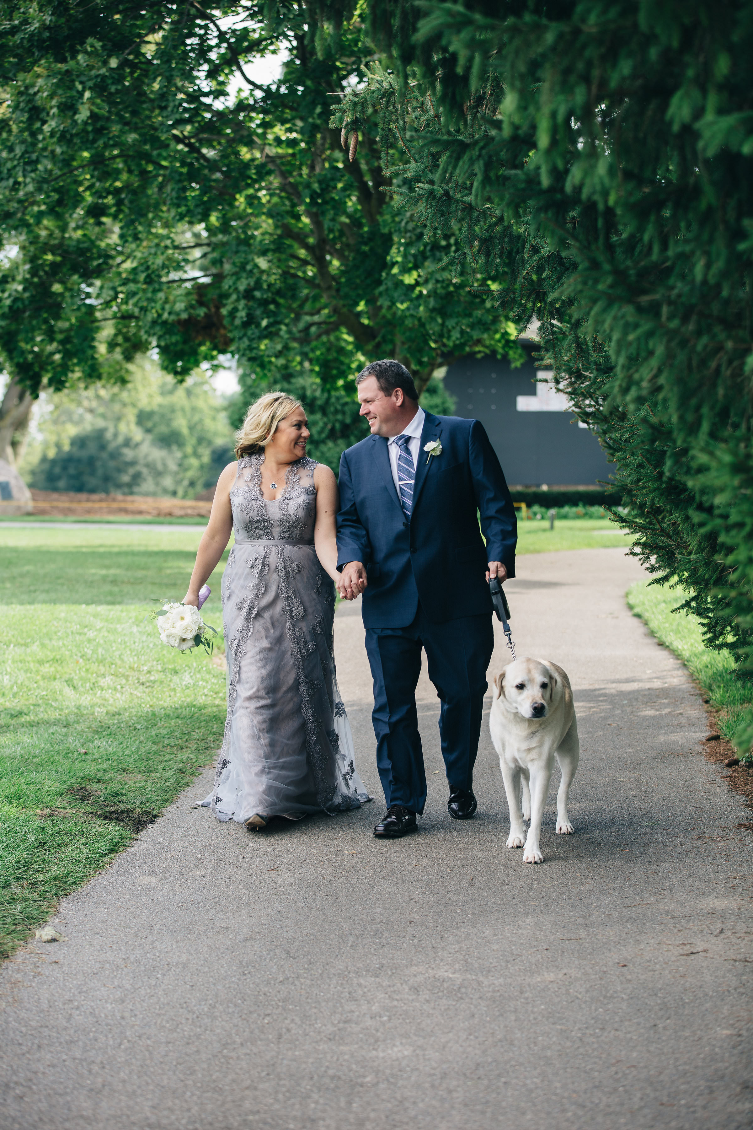 Bride and groom with dog on wedding day.