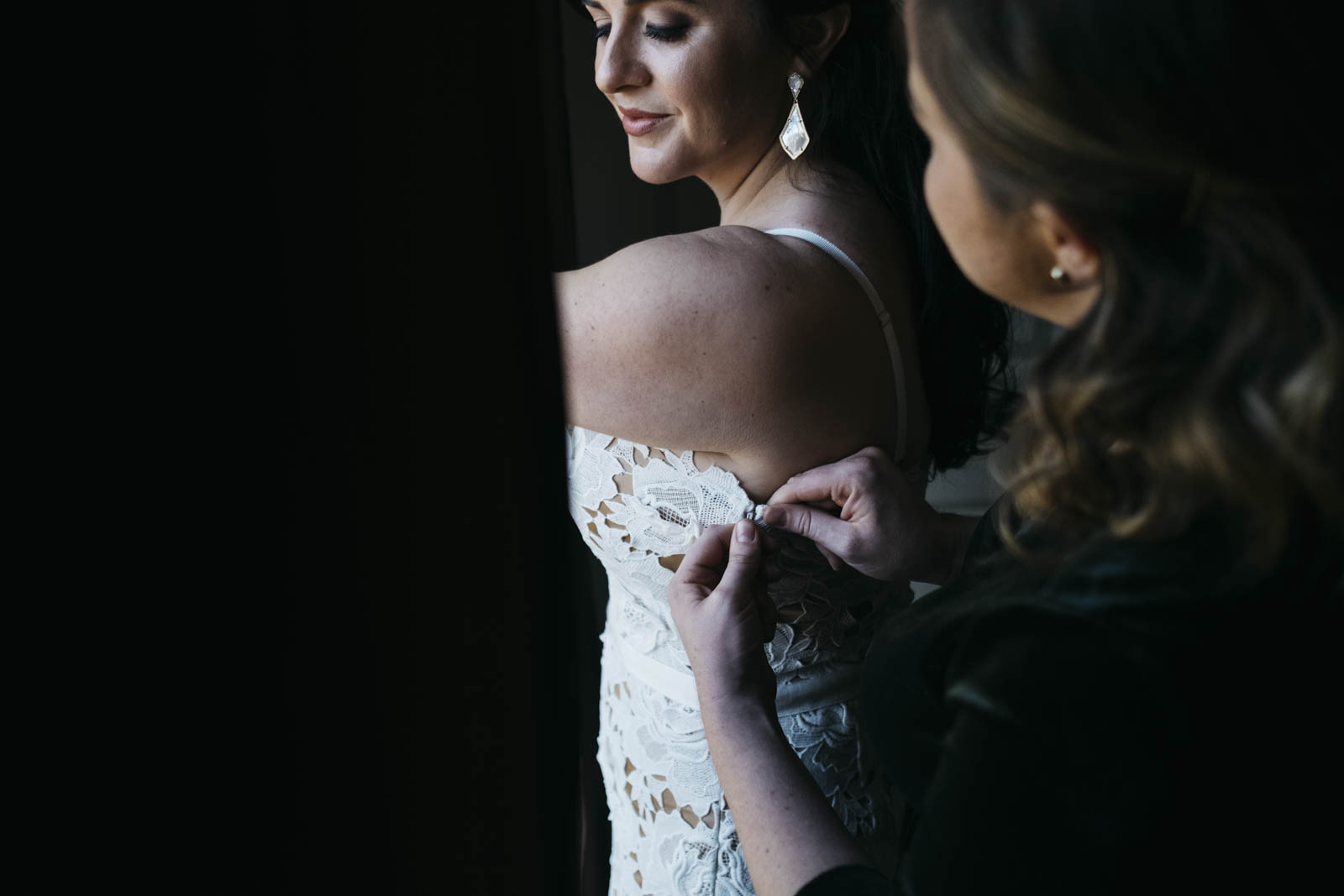 Bride getting into dress on wedding day.