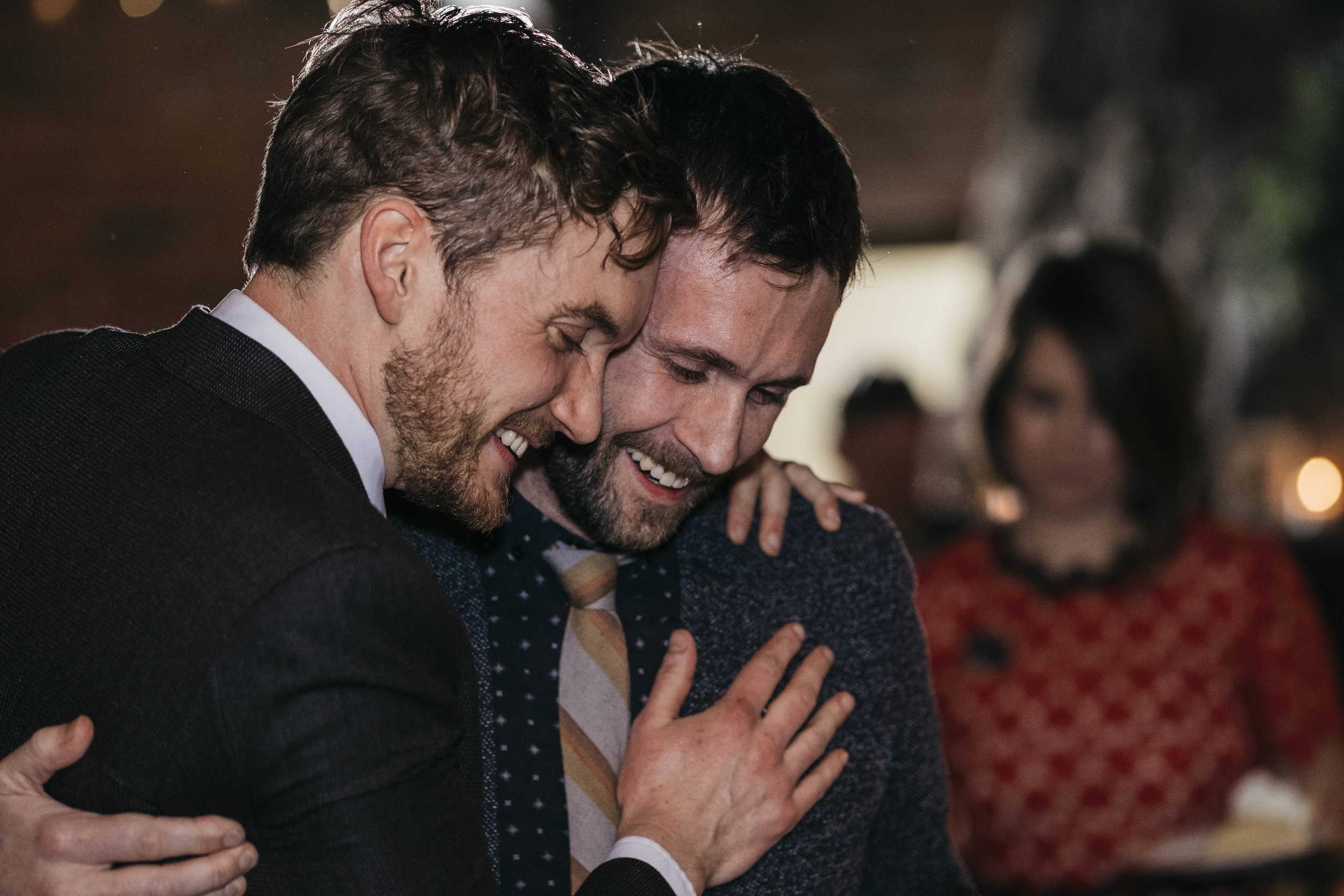 Groom laughs with friend during speeches at his wedding reception.