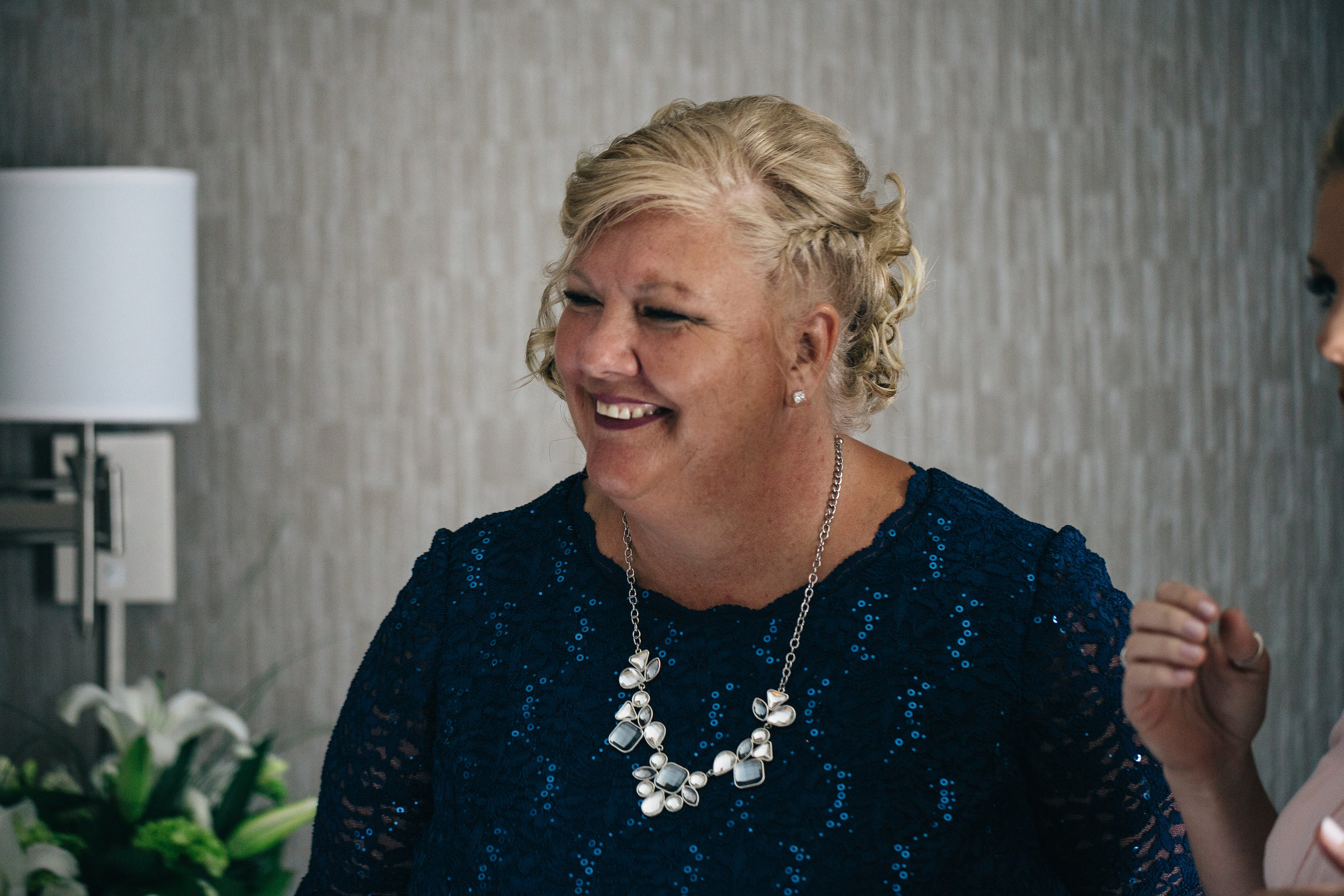 Mother of the bride smiles while her daughter gets ready for her wedding ceremony.