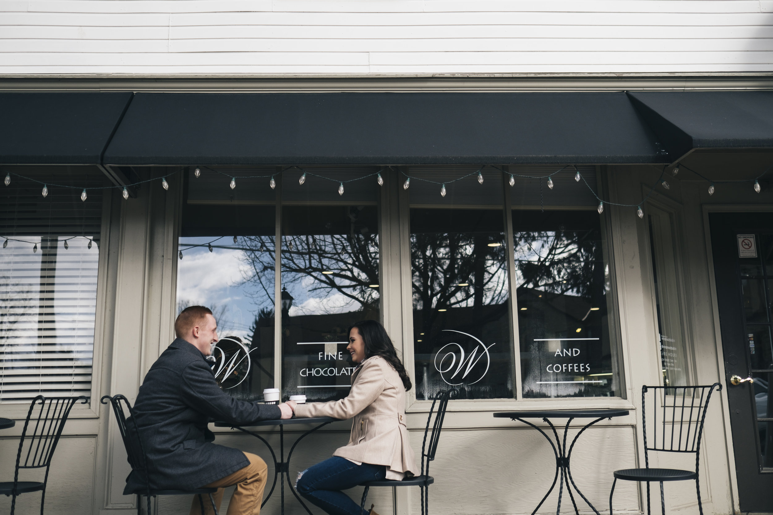 Couple sitting outside Winans Fine Chocolates and Coffees during engagement session.