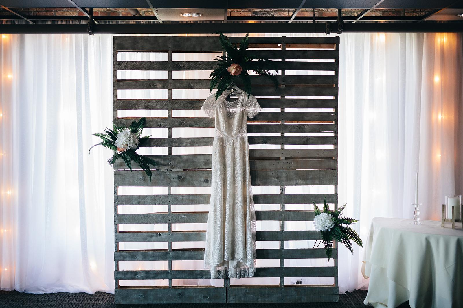Wedding dress hangs on DIY ceremony backdrop in Toledo, Ohio.
