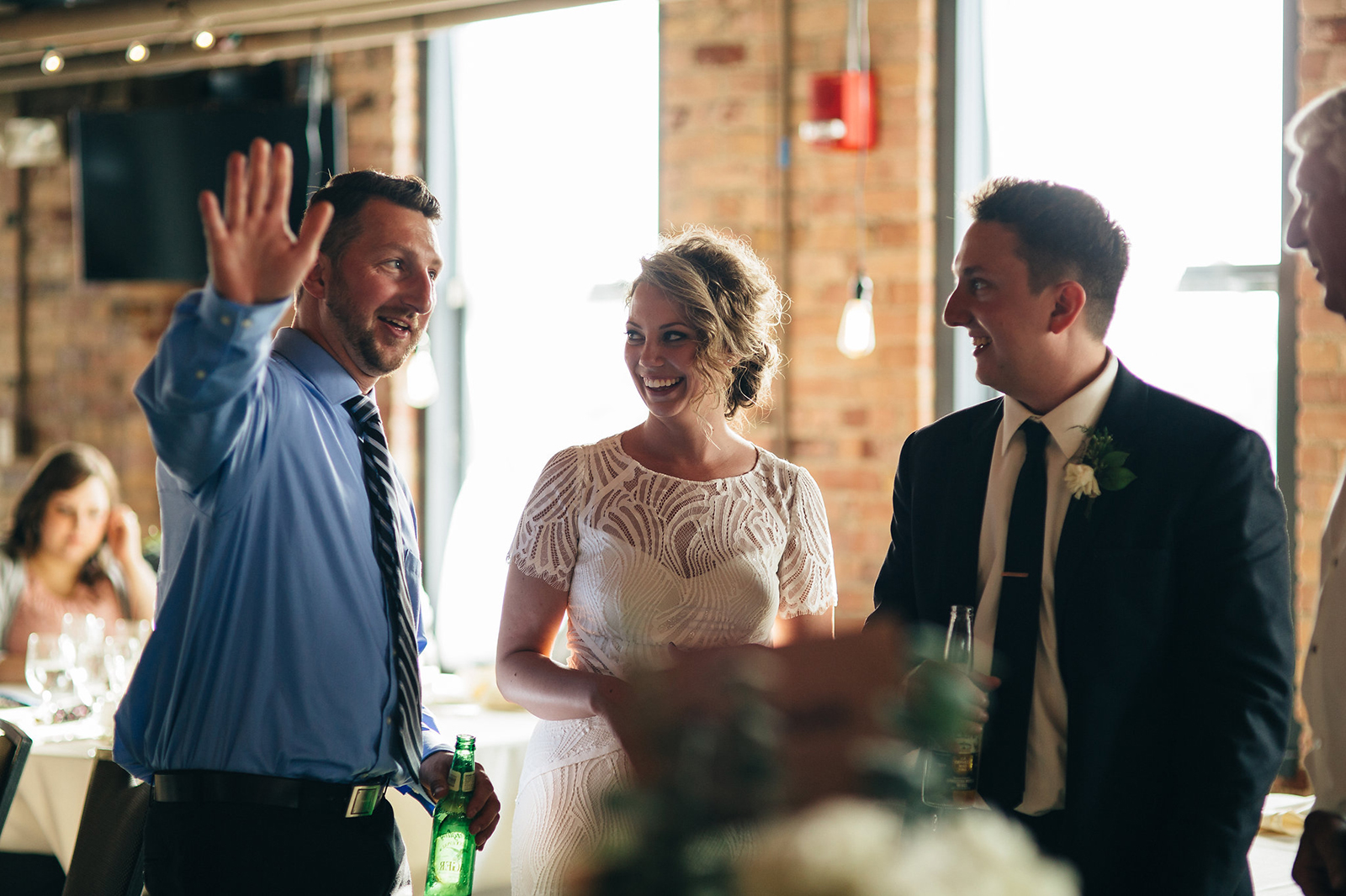 Bride and groom talk to guest at their wedding.