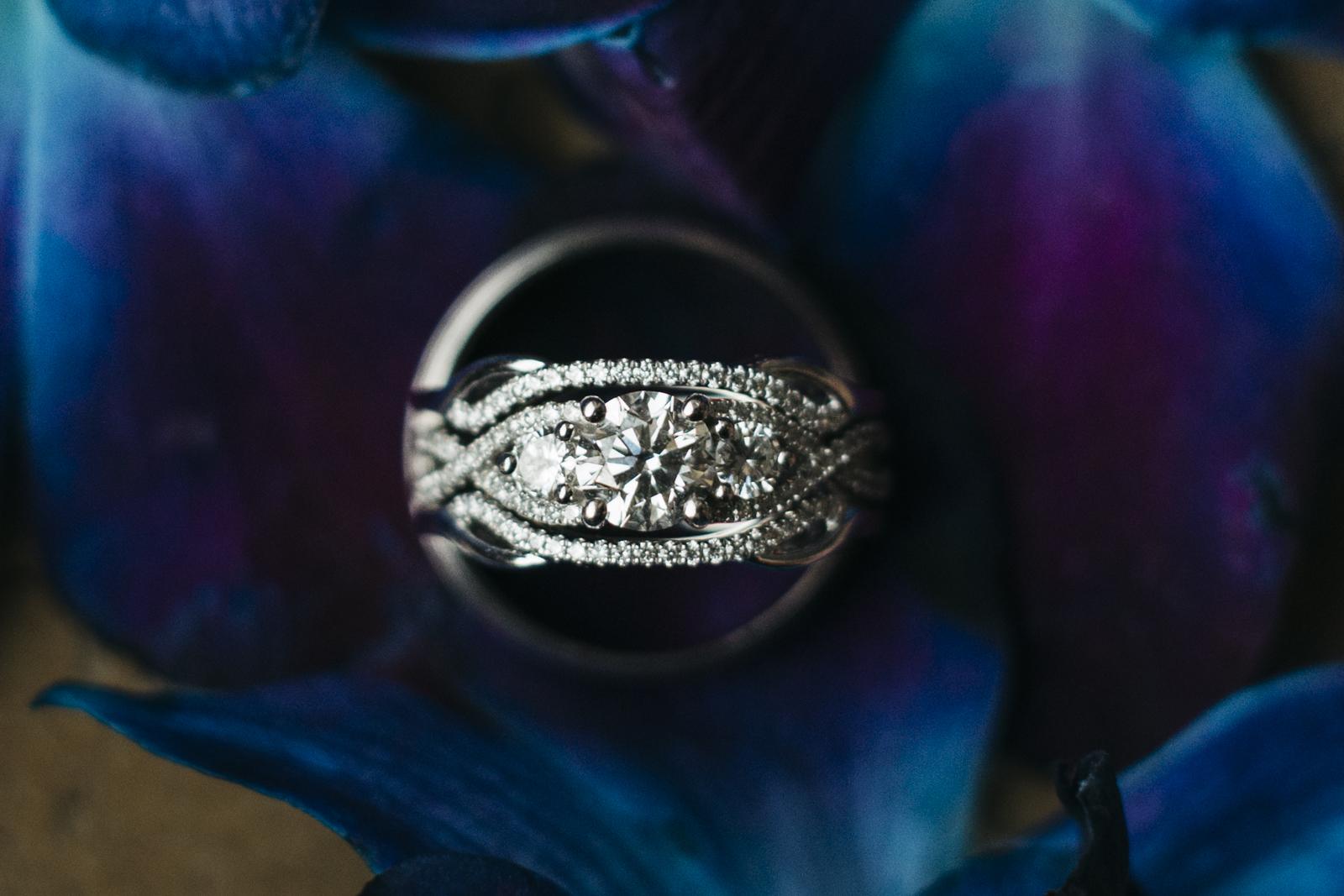 Diamond wedding ring photography in purple flowers.