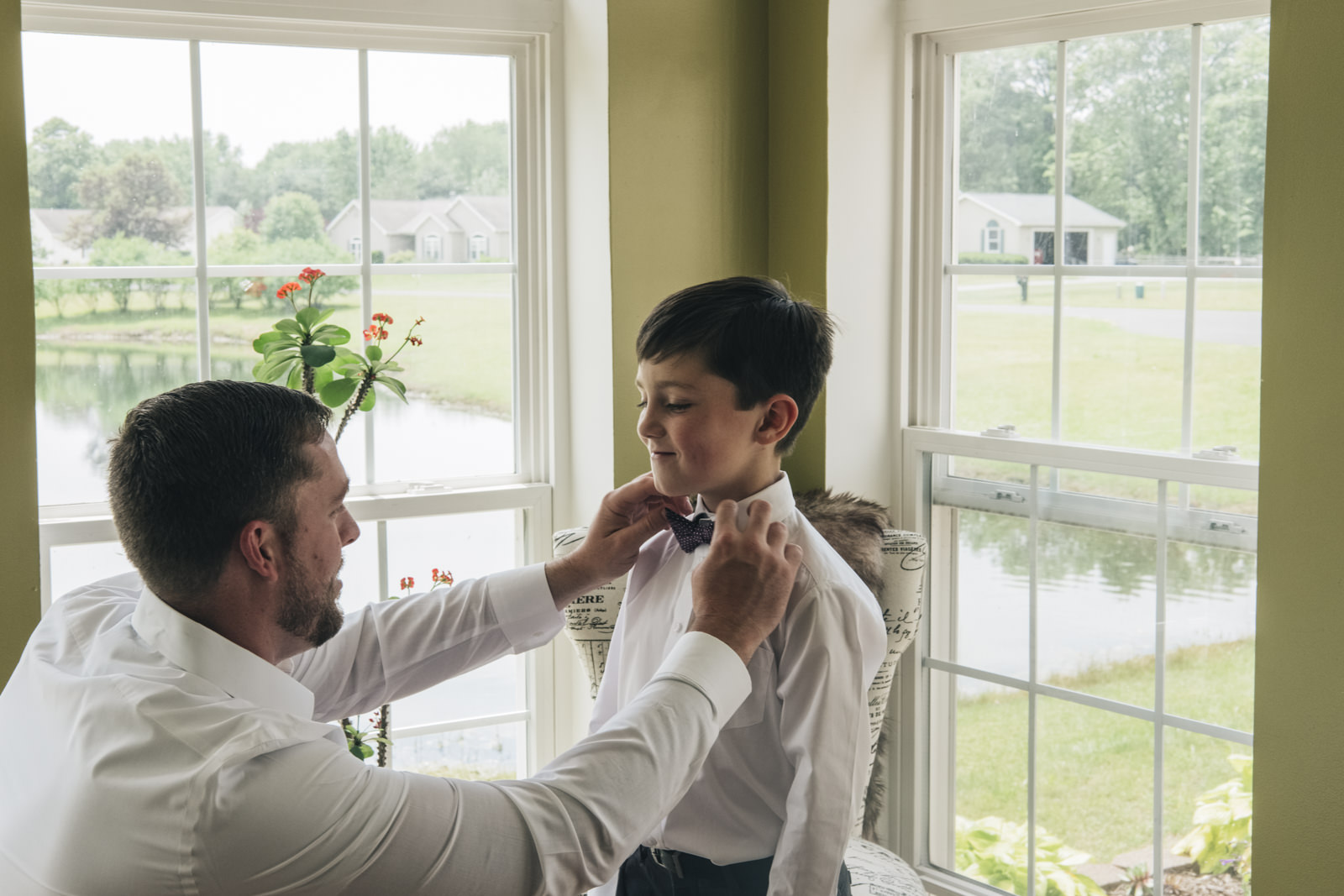 Groom-to-be getting son ready on wedding day.
