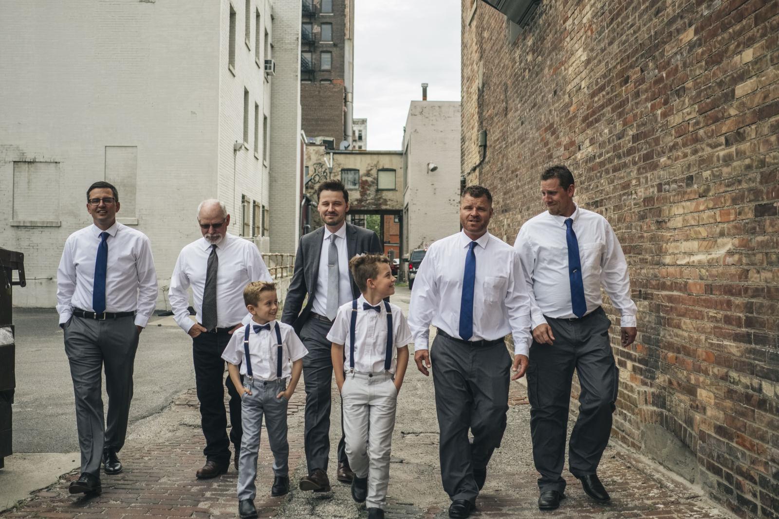 Groom and groomsmen walk down an ally in downtown Toledo.