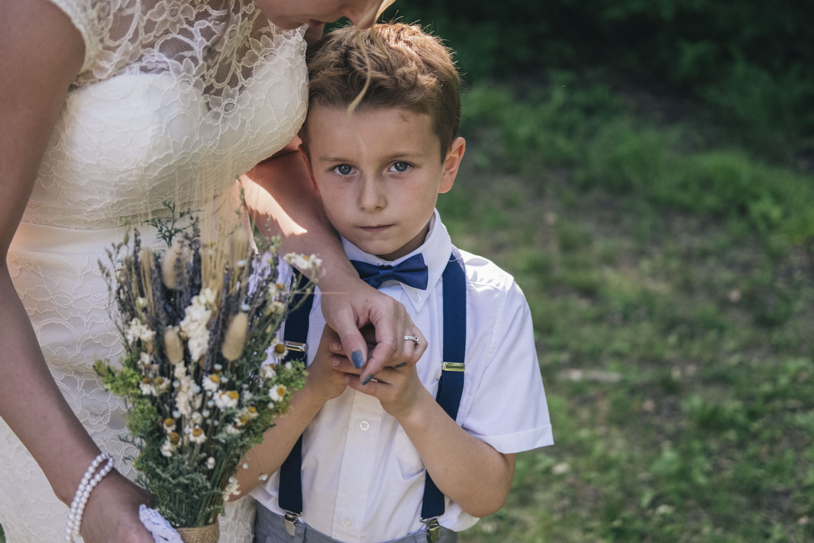 Ring bearer holds mom's hand during wedding pictures.