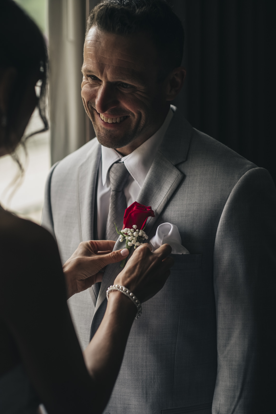 Bride helps groom get ready before their elopement.