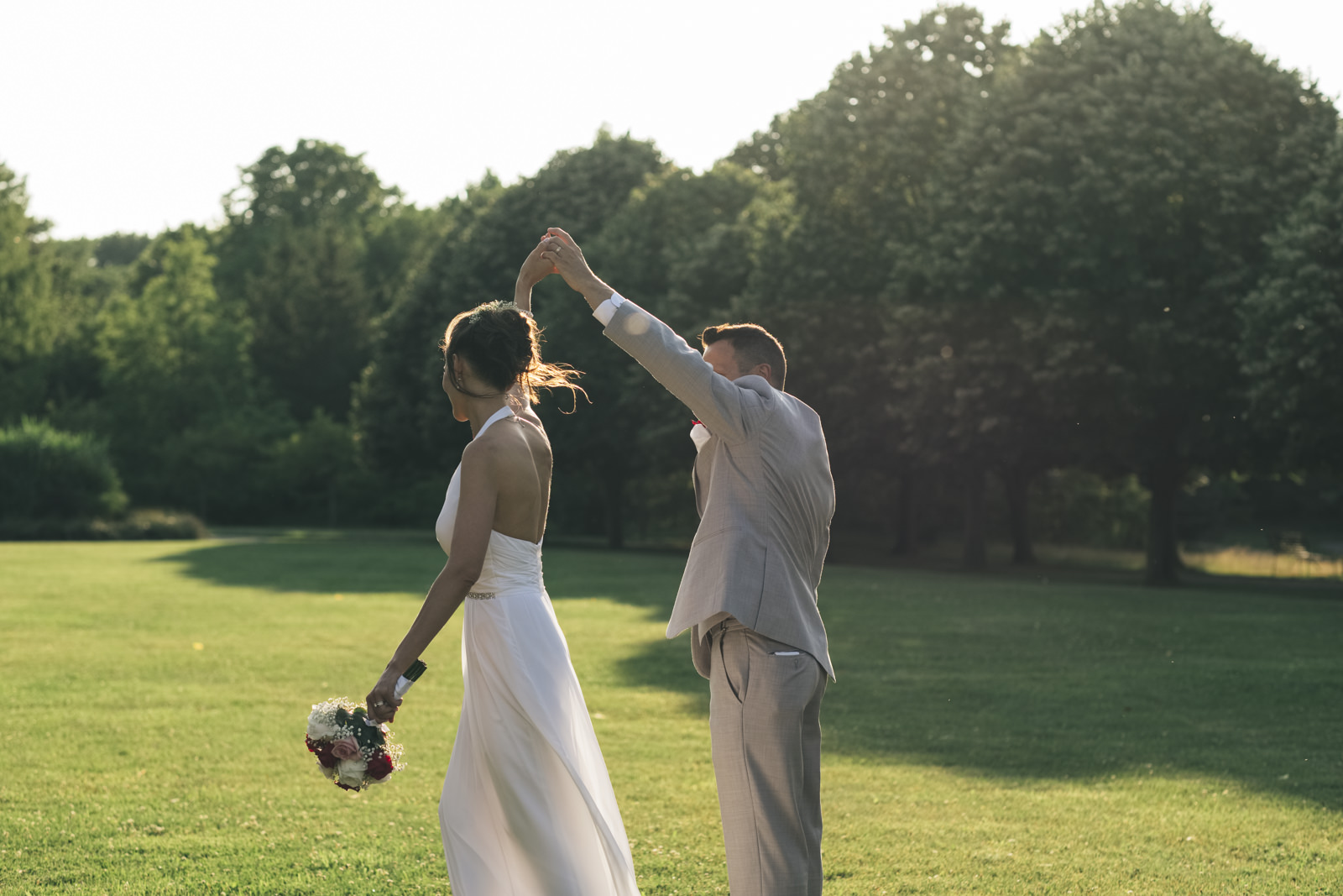 Bride and groom dance in a field after their wedding reception.