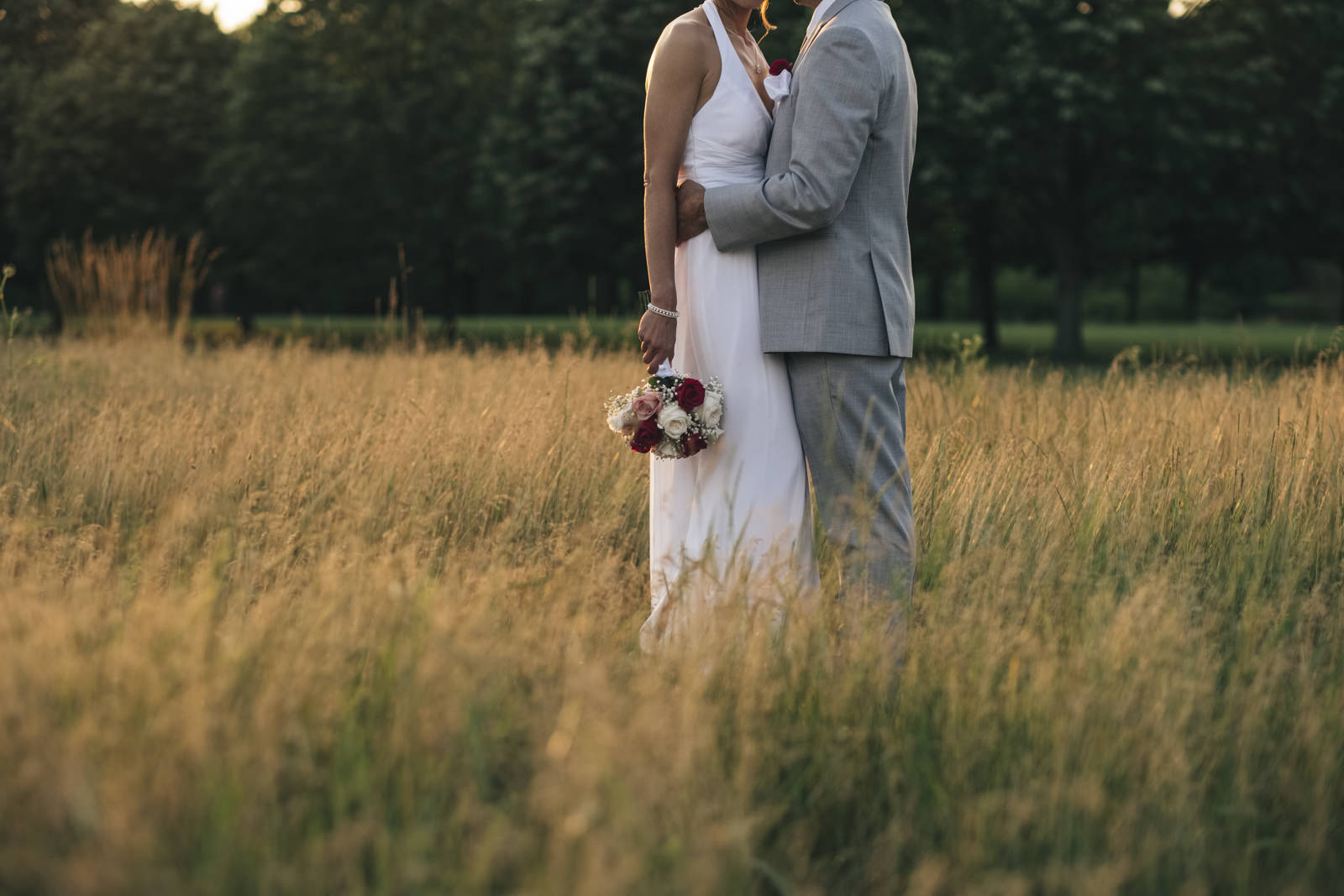 Bride and groom kiss in a field during golden hour in Ohio.