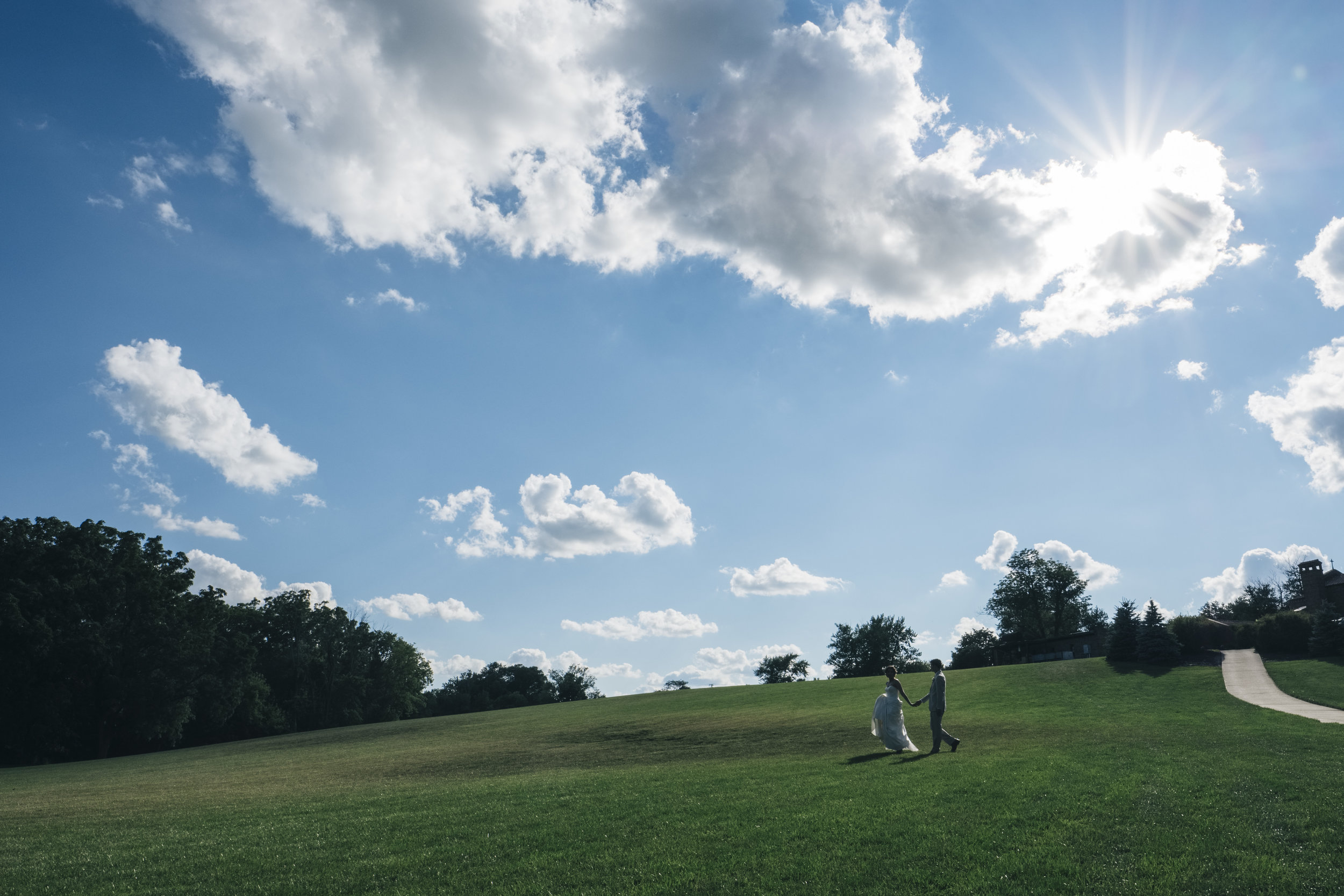 Bride and groom walk out in a field outside of Nazareth Hall.