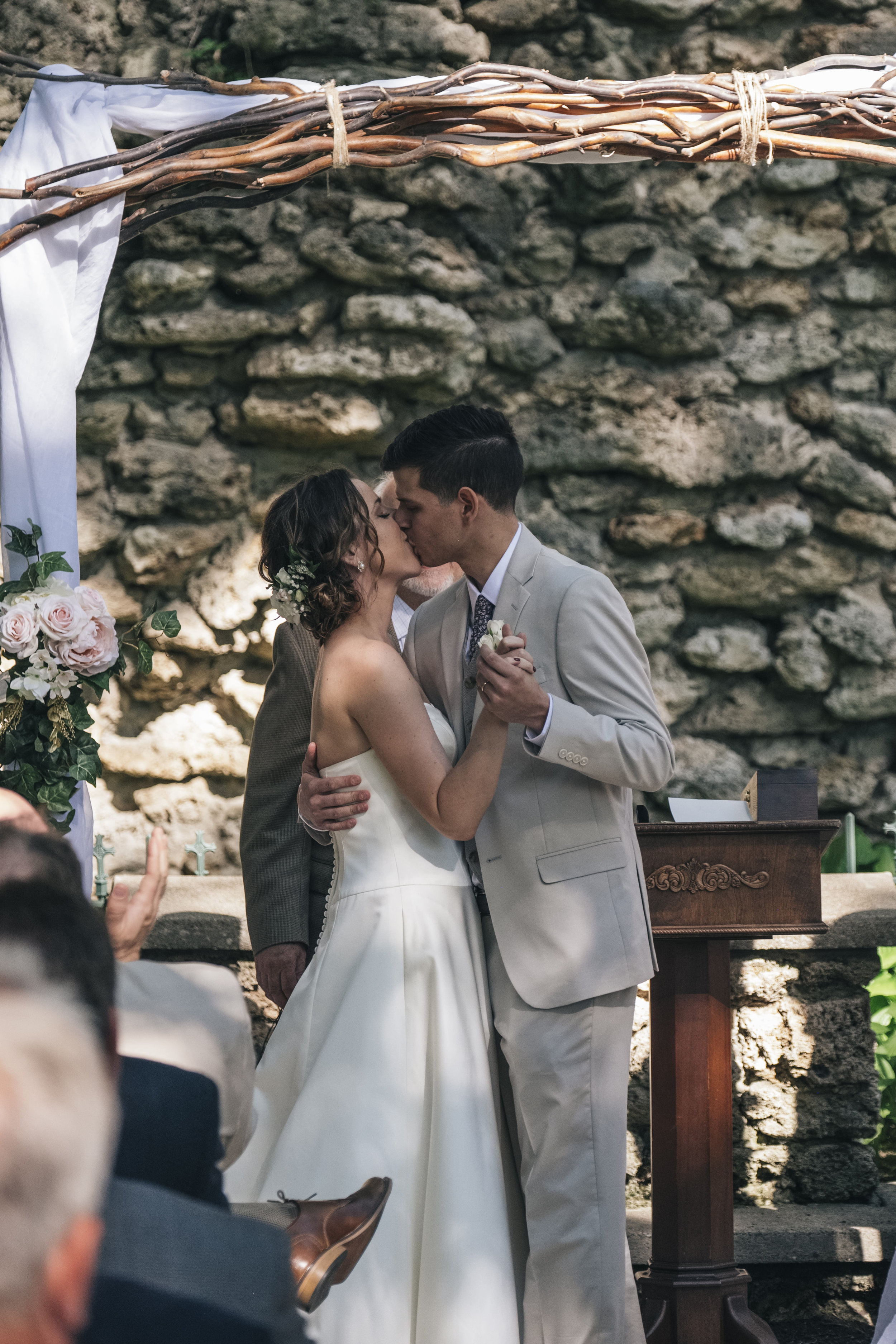 The bride and groom kiss during their wedding ceremony at Nazareth Hall.