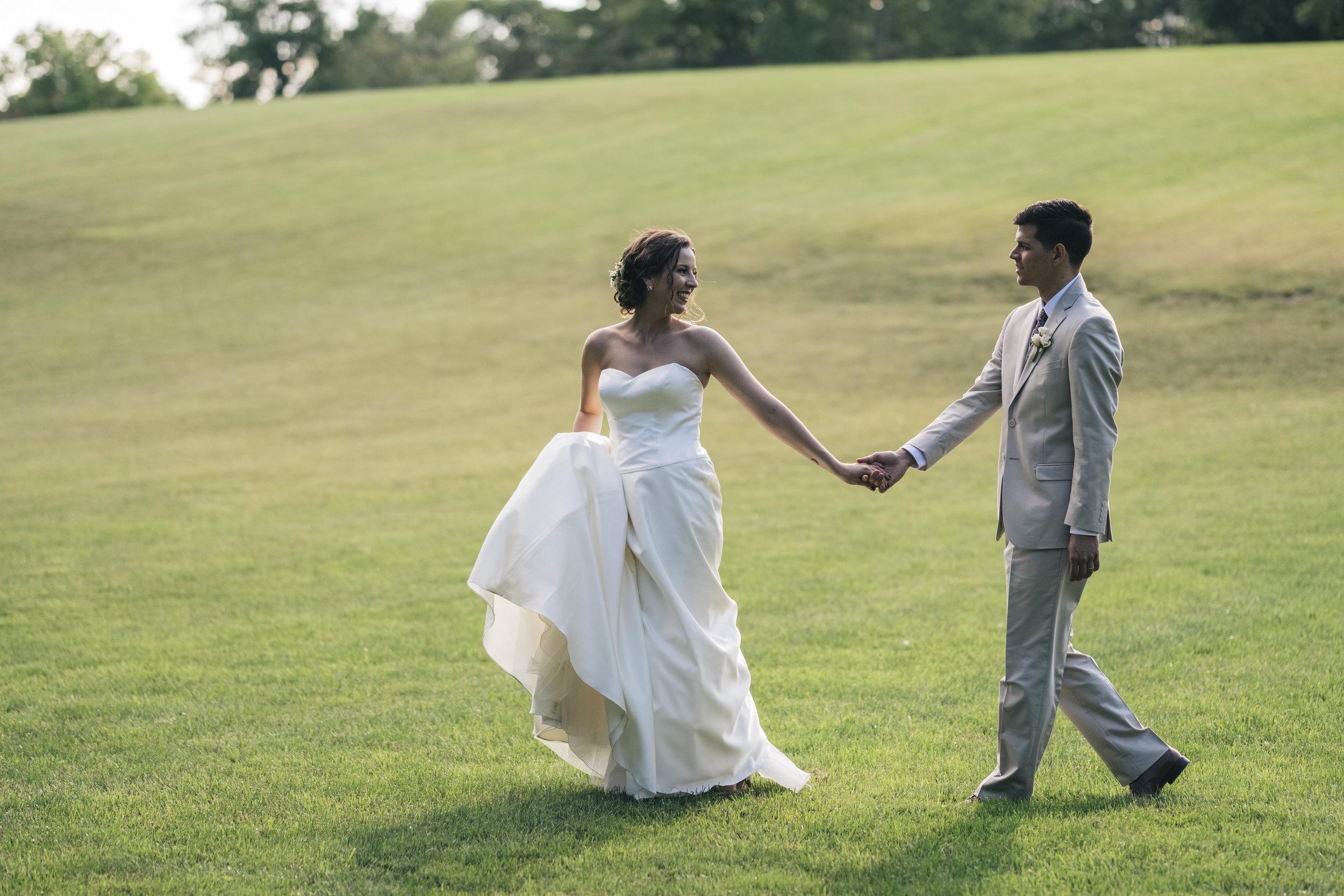 Bride and groom walk across Nazareth Hall grounds in Grand Rapids, Ohio.