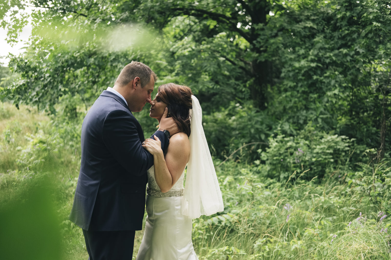 Bride and groom share a kiss before their wedding ceremony at Swan Creek Park.