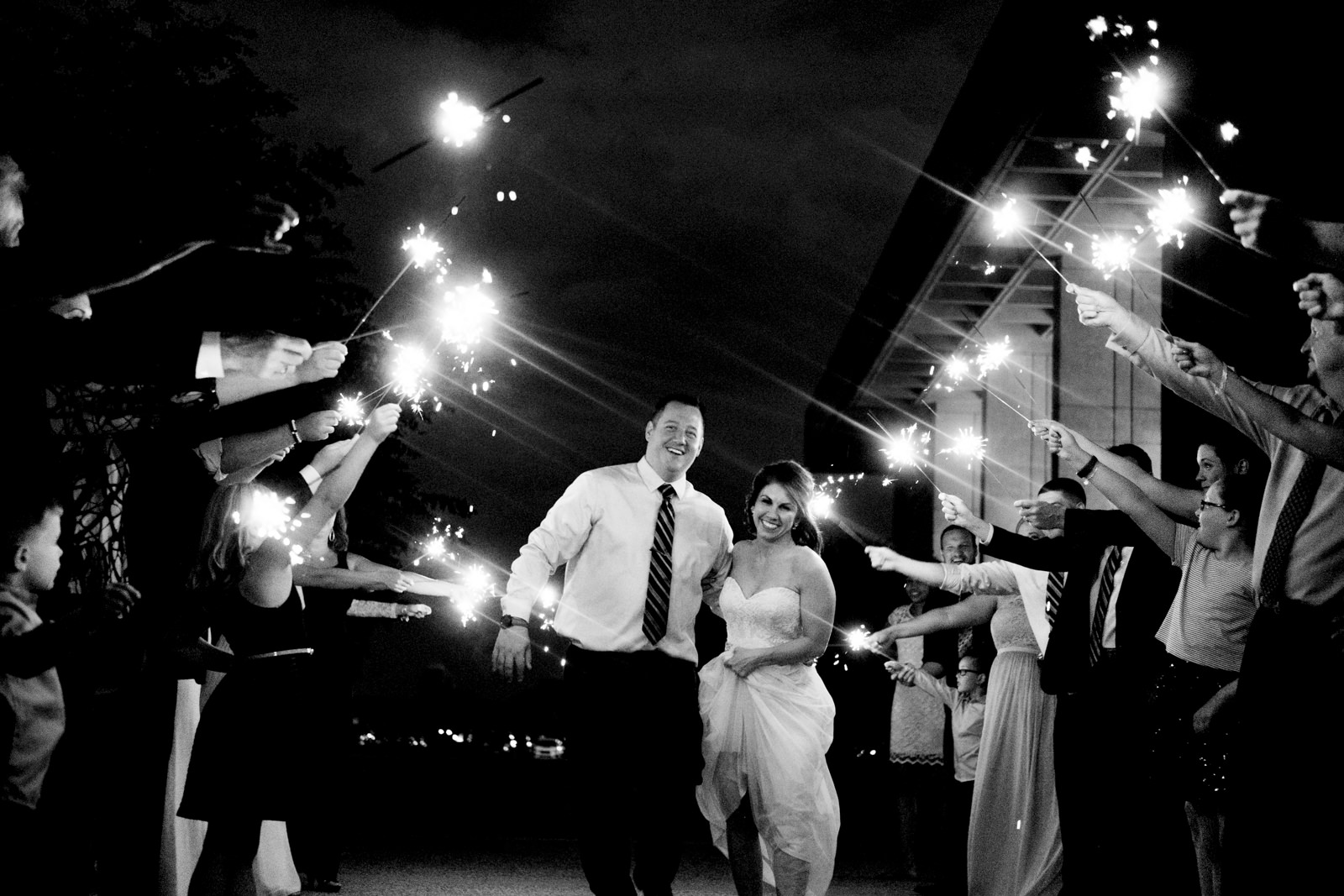 Bride and groom leave their ceremony walking through a great sparkler exit of family and a friends at Stranahan Theatre in Toledo, Ohio.
