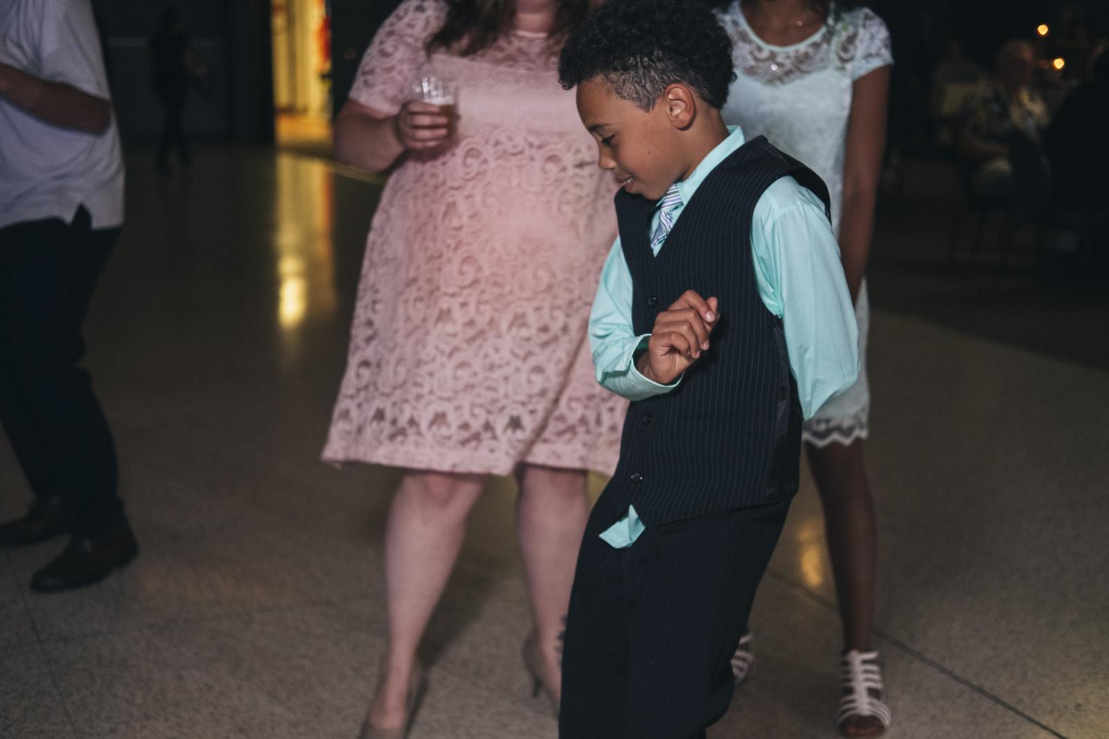 Little boy dances at his family's wedding reception.