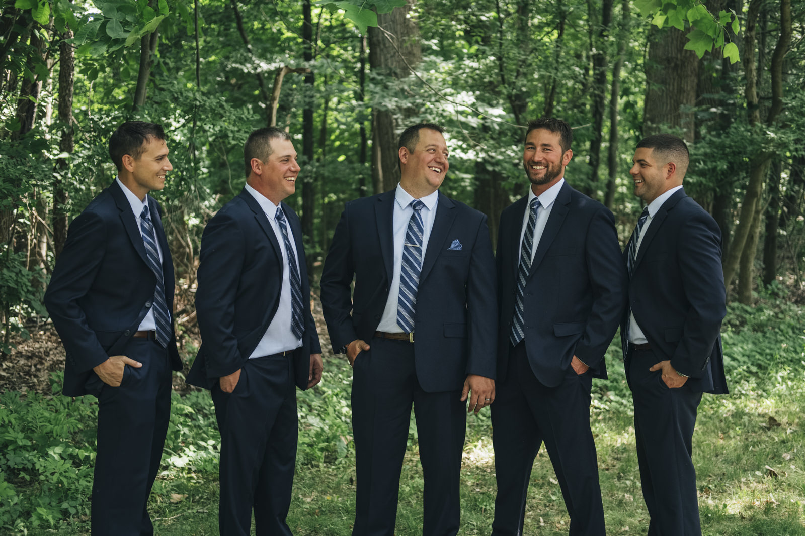 Groomsmen laughing with the groom before the wedding ceremony at Stranahan Theatre.