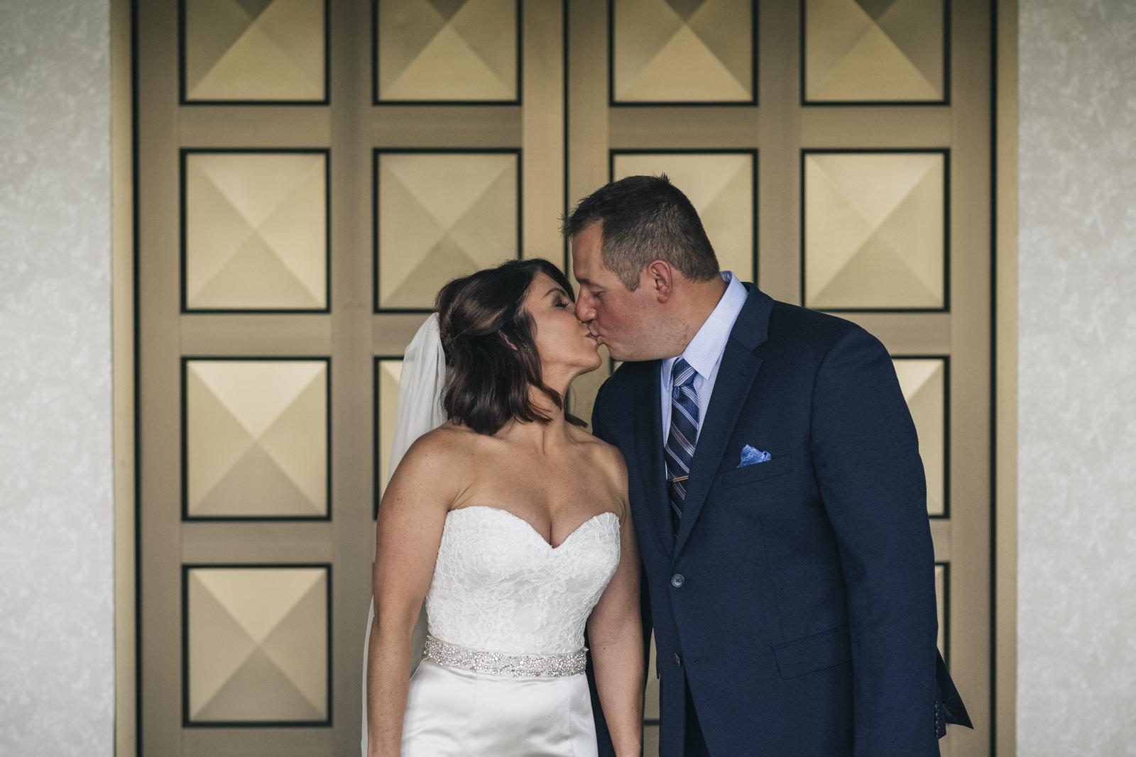 Bride and groom kiss in front of the theater doors in Toledo, Ohio.