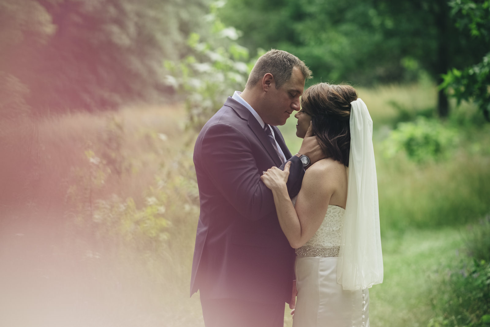 Bride and groom lean in for a kiss before their wedding ceremony at Swan Creek Park.