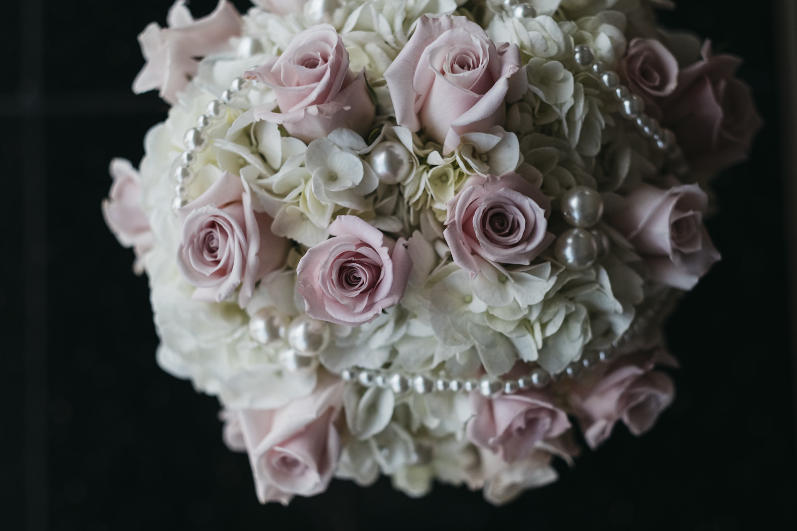 Bridal bouquet with blush and white flowers and pearl accesories.