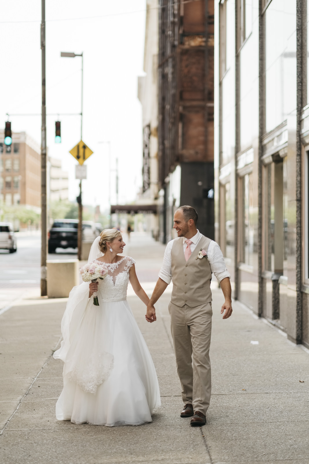 Bride and groom walk through downtown Toledo.