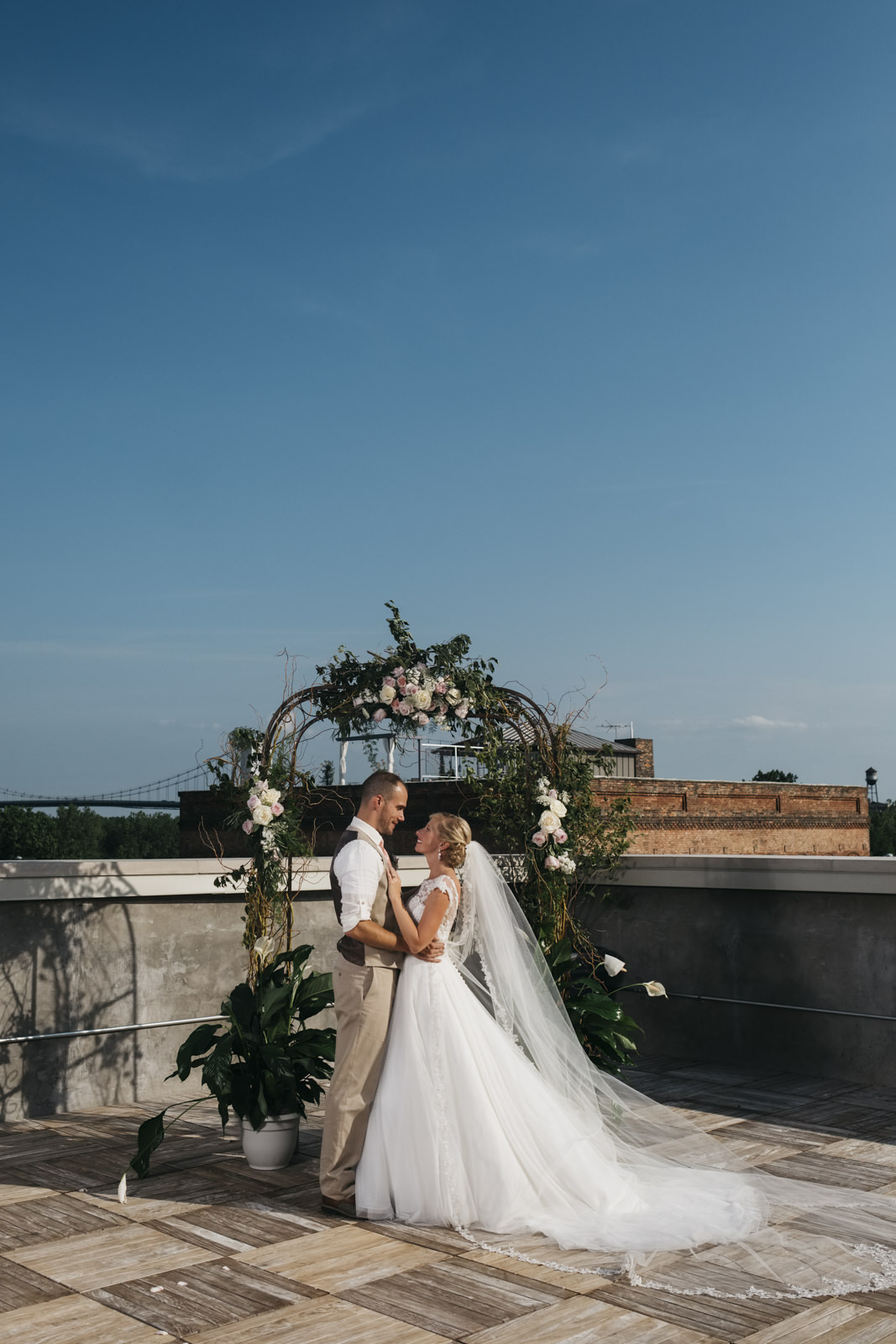 Bride and groom stand under their archway on a rooftop in downtown Toledo.