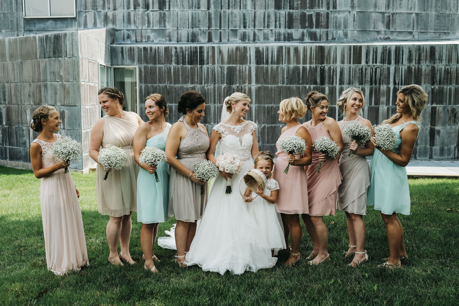 The bridesmaids wear a mix of blue and blush dresses for the bride's wedding in downtown Toledo, Ohio.