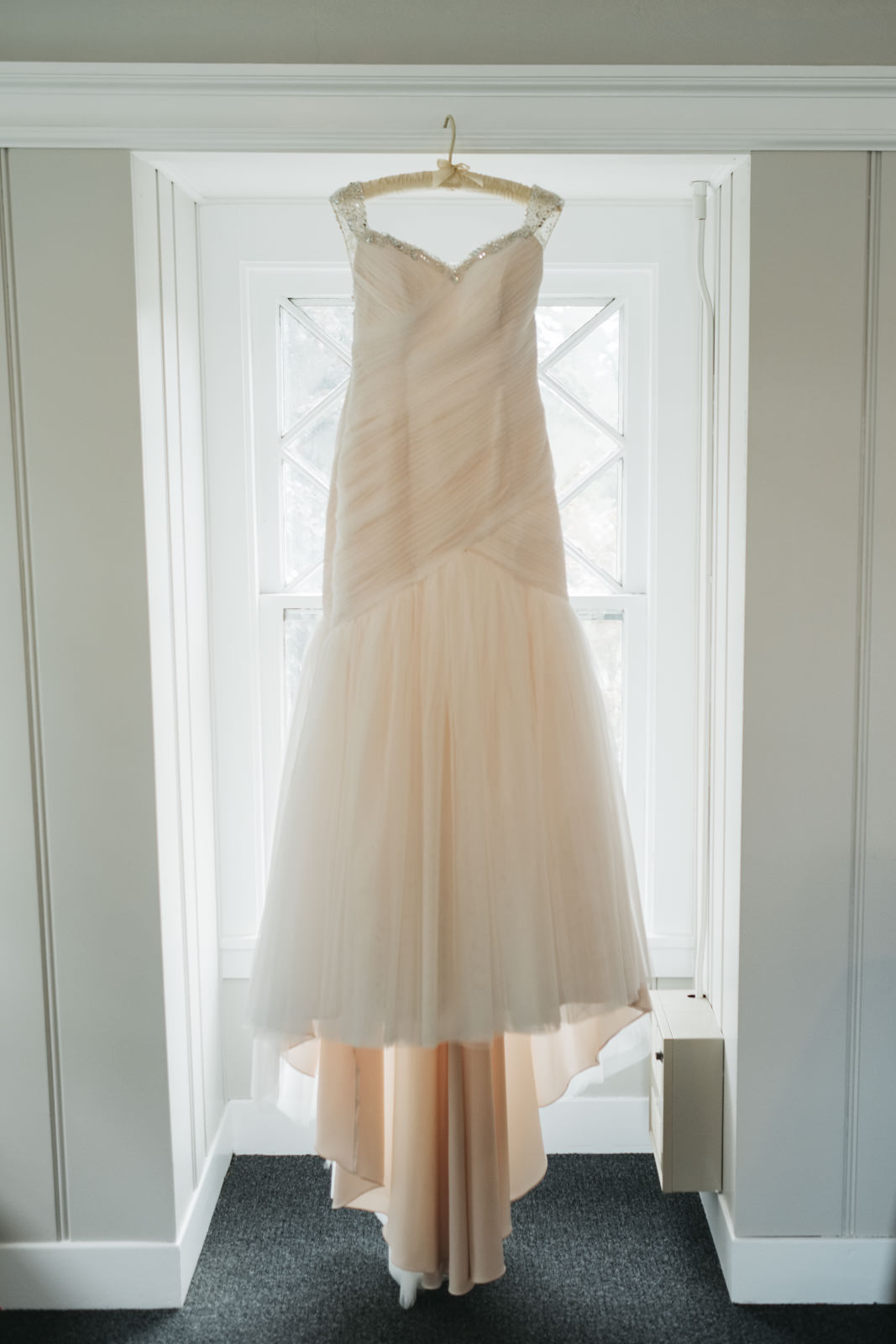 The bride's dress hanging in a doorway