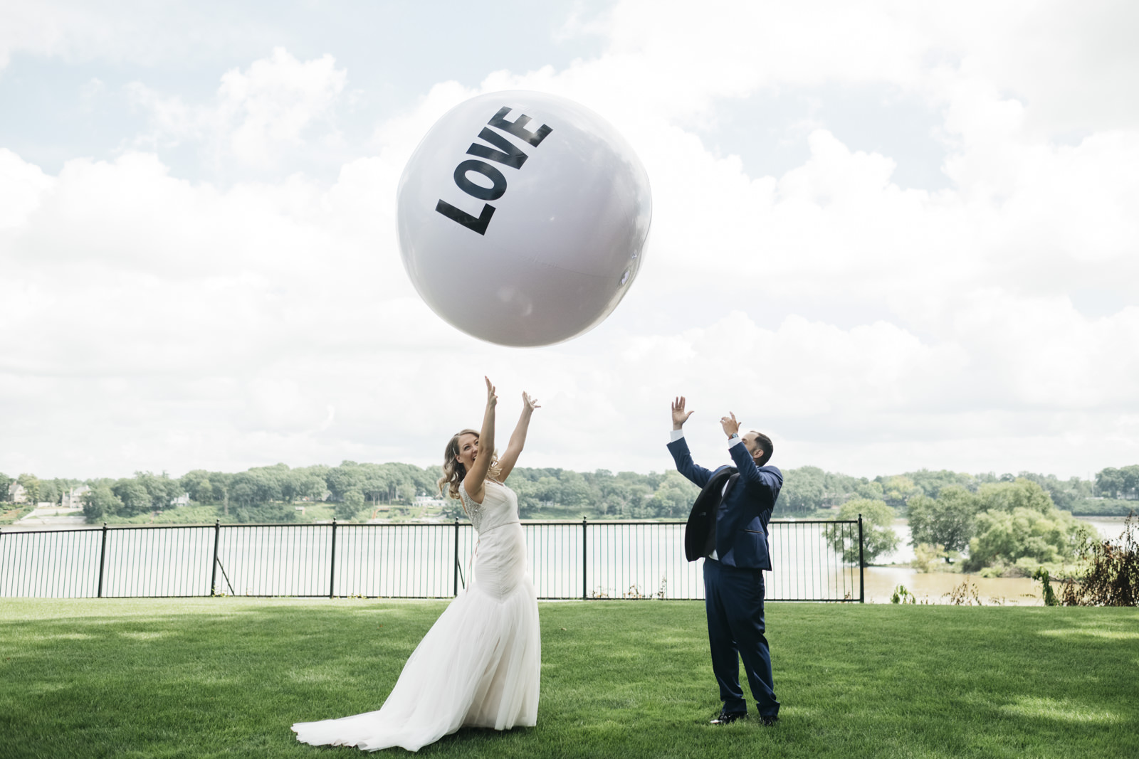 Bride and groom have fun with a giant love ball at their wedding.
