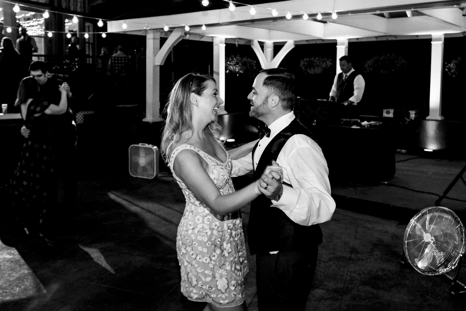 Black and white photo of bride and groom dancing at wedding reception.
